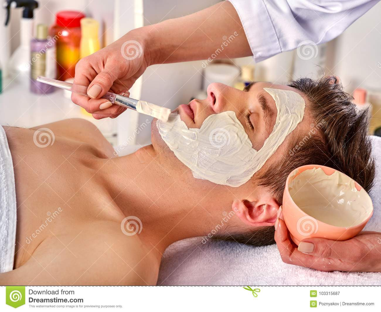 Mud facial mask of woman in spa salon. Face massage.