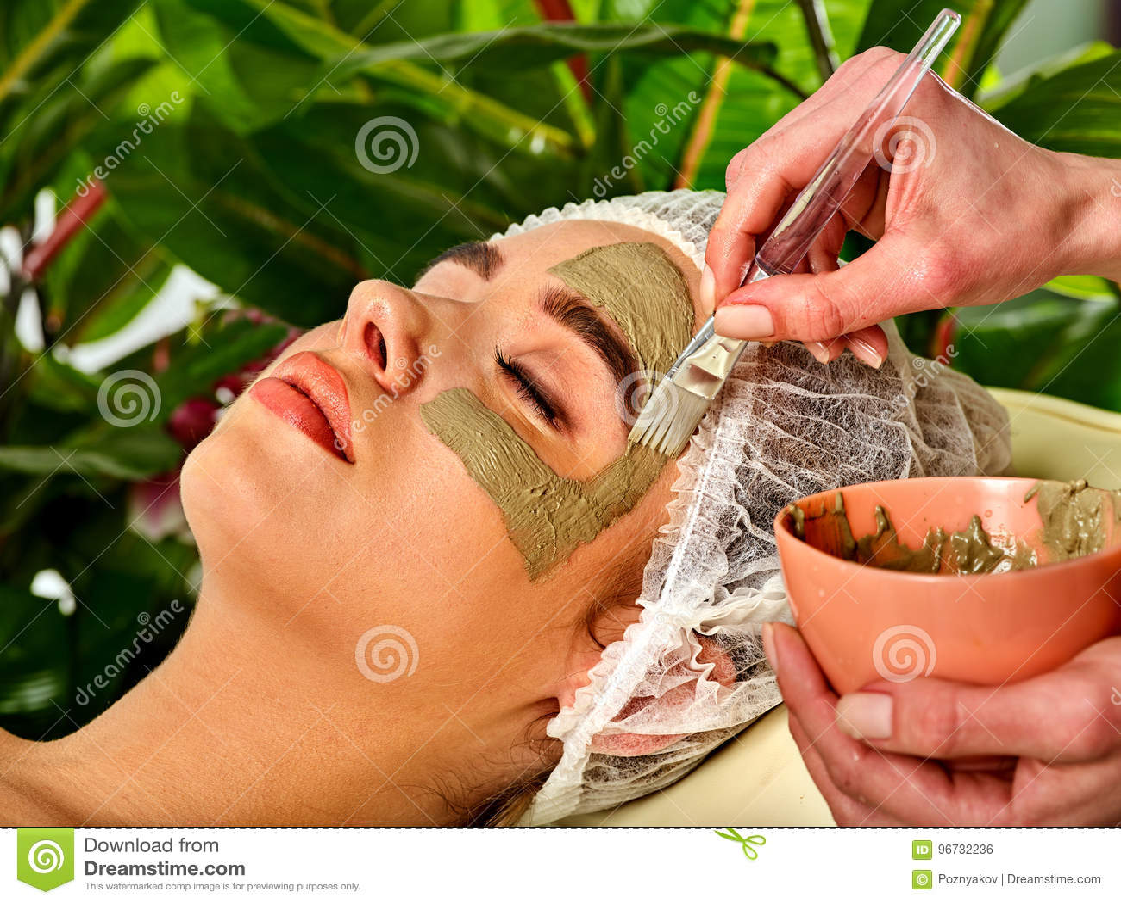 Mud facial mask of woman in spa salon. Face procedure .
