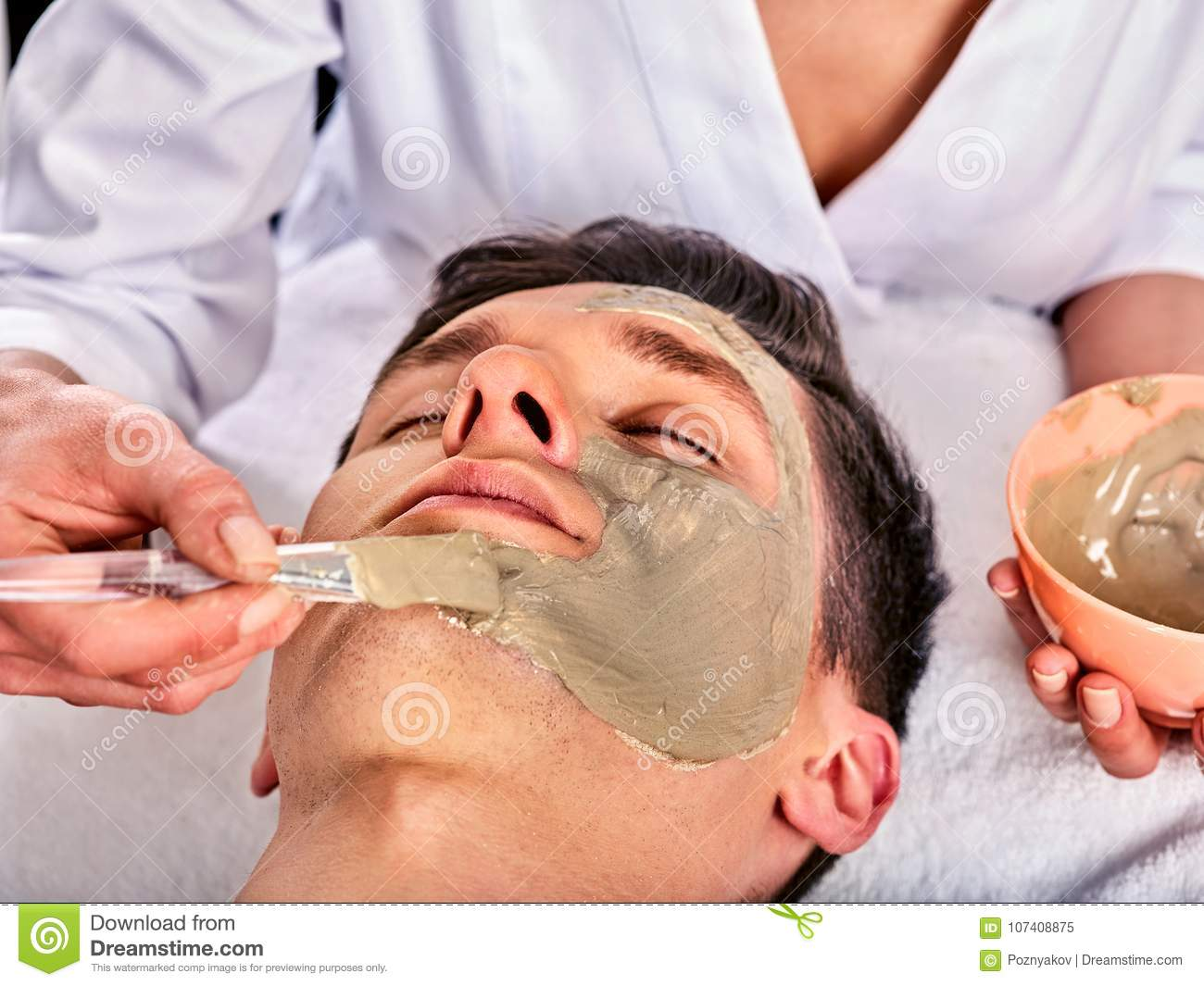 Mud facial mask of woman in spa salon. Face massage .
