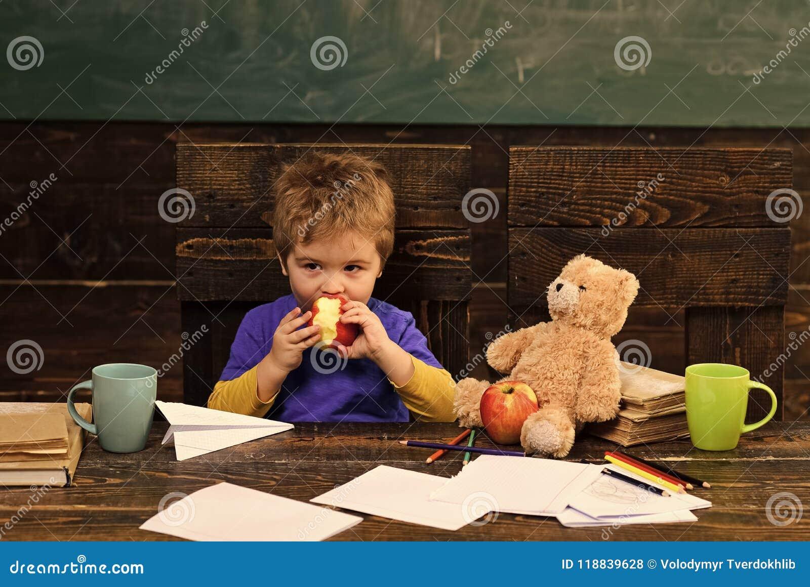 Mudança da escola Ruptura da escola Maçã cortante da criança com fome na sala de aula Menino pequeno que joga com o urso de papel