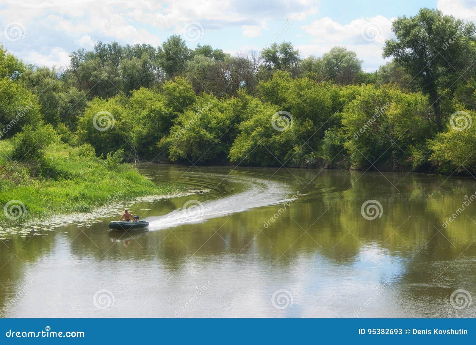 Mudanza encendido de un barco de motor en un río con las costas boscosas