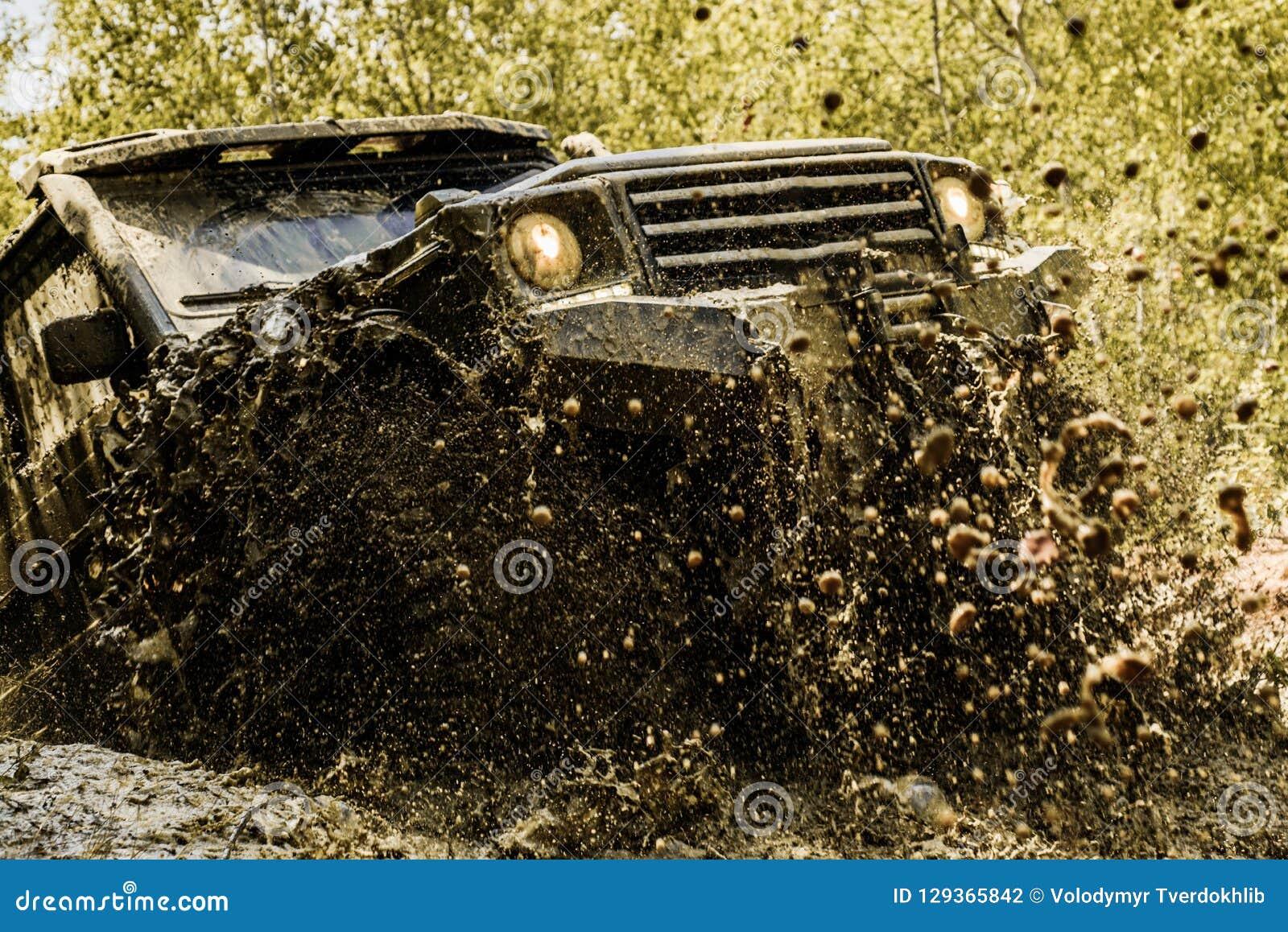 Mudding off-roading till och med ett område av våt gyttja eller lera Spår på gyttja Vinka den hjulgummihjulen och av-vägen som gå