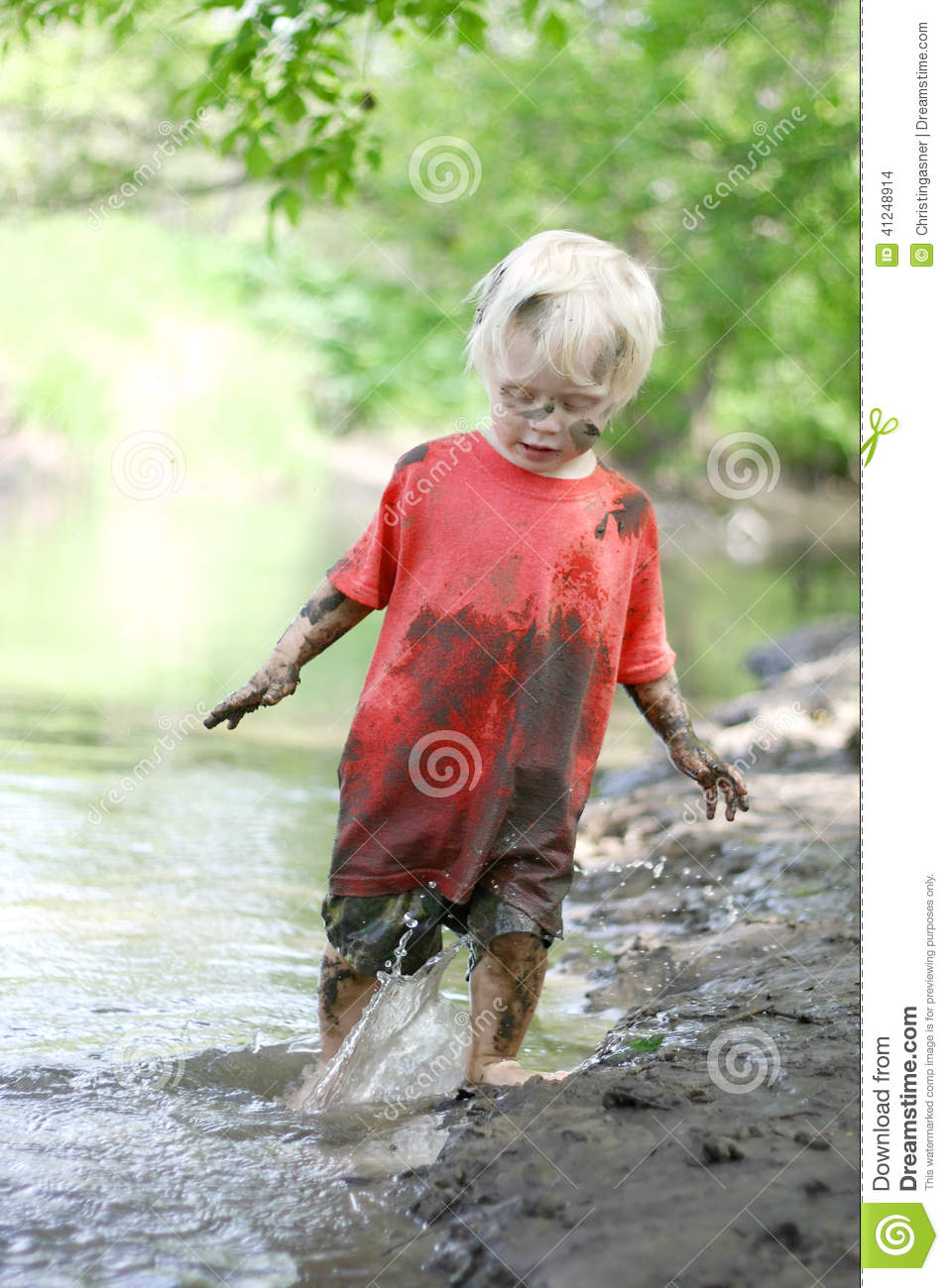 Muddy Little Boy Playing Outside nel fiume