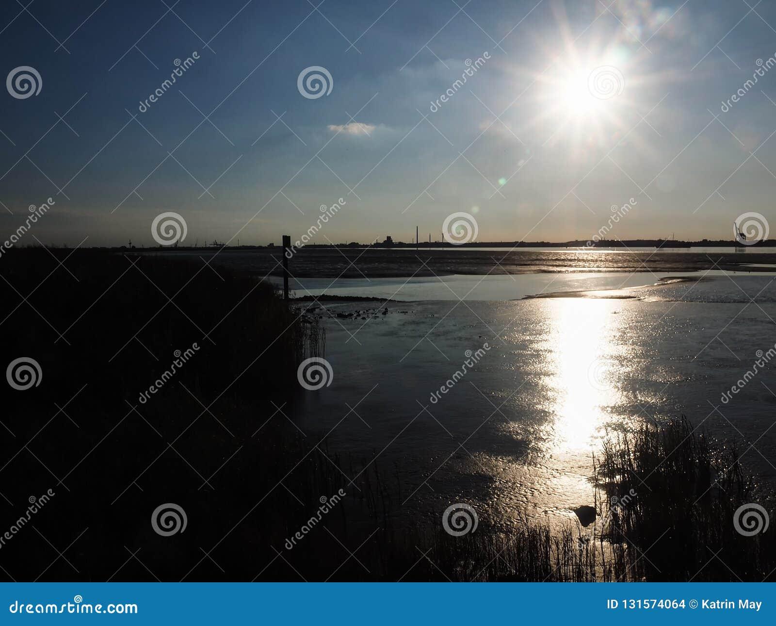 Mudflats in het estuarium van Weser-rivier dichtbij Nordenham bij backlight