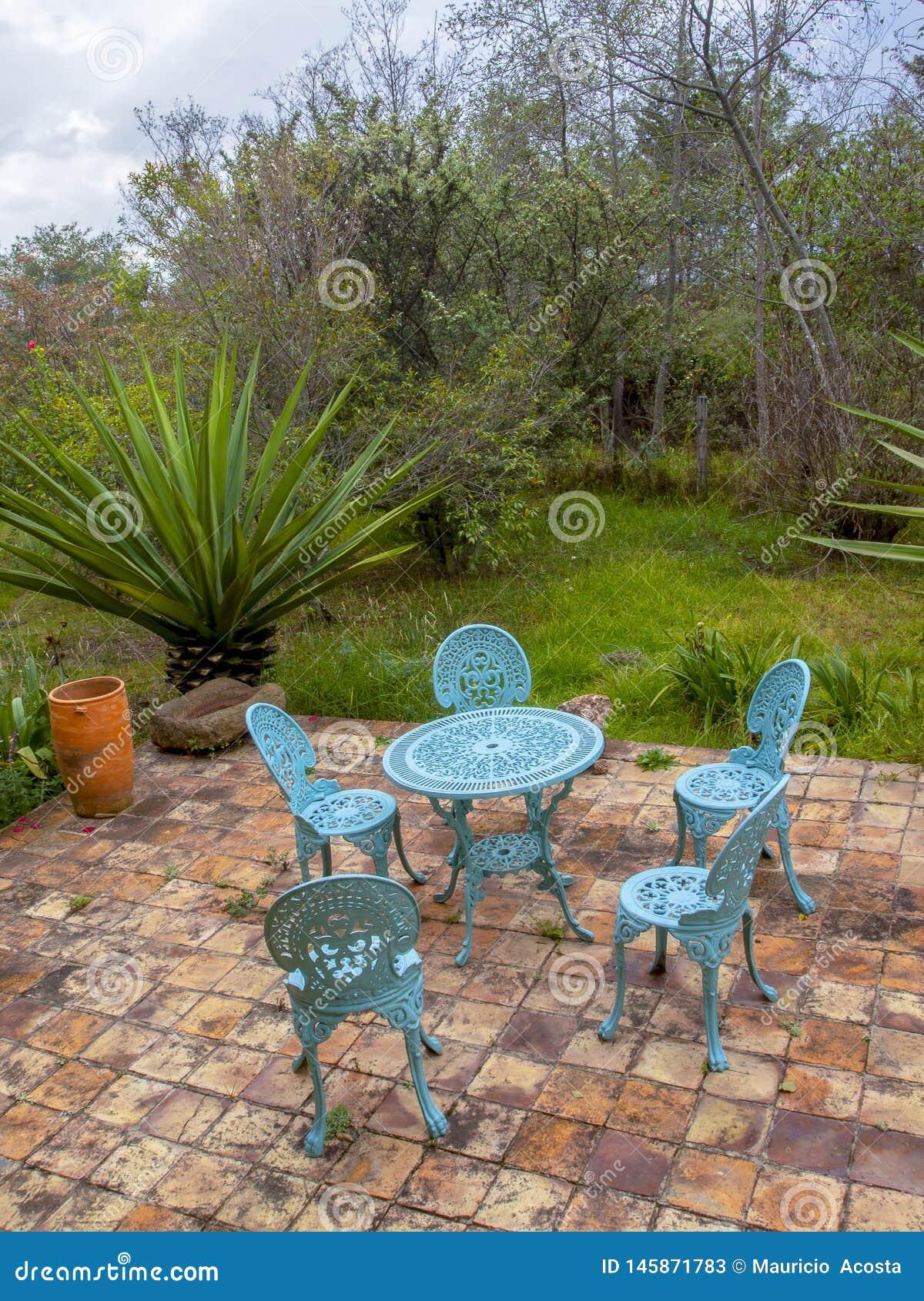 Muebles metálicos del jardín en una terraza de la teja de la arcilla