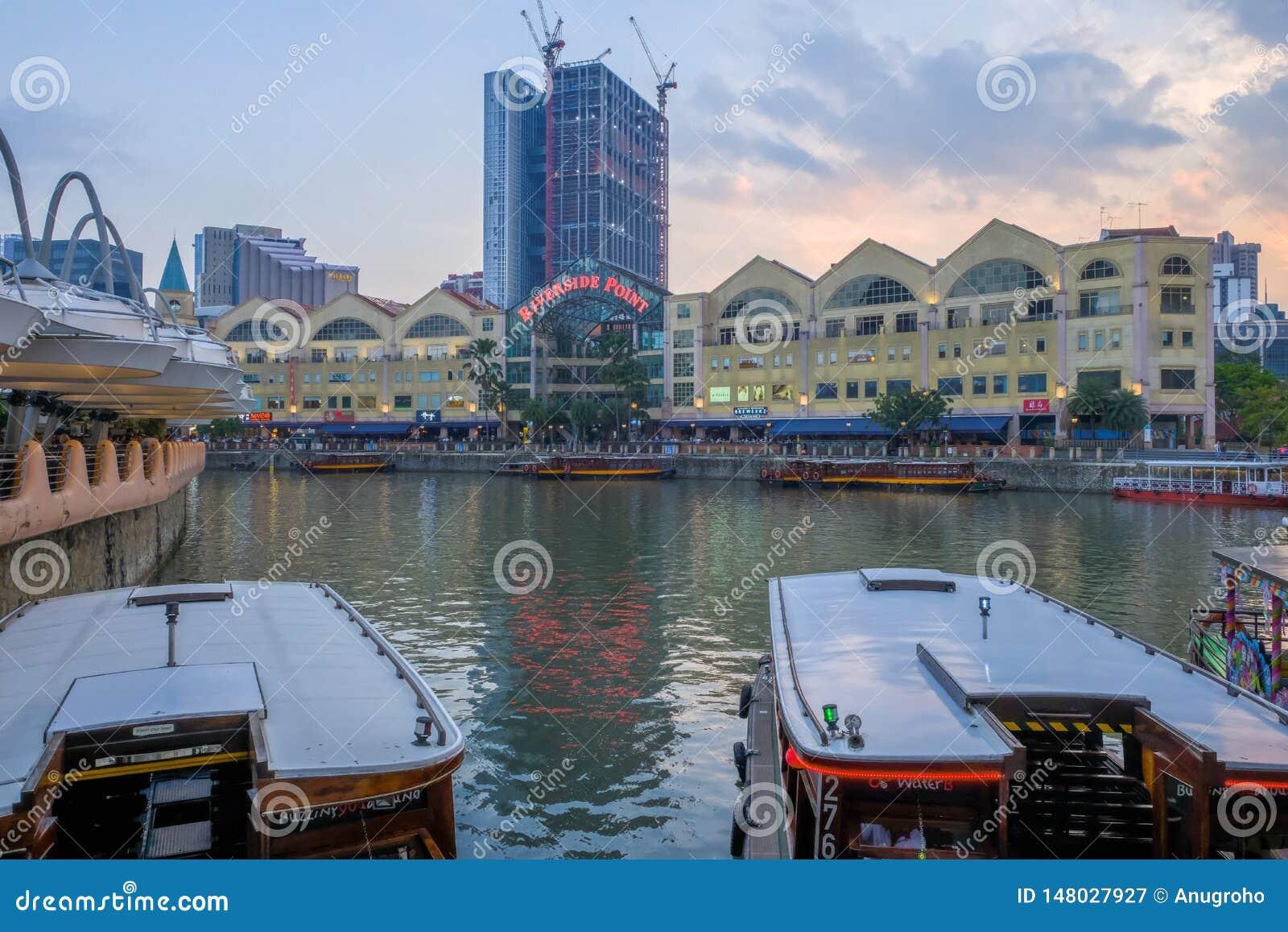 MUELLE de CLARKE, SINGAPUR - 7 de marzo de 2019: Un bumboat tradicional en el r?o de Singapur con el edificio del punto de la ori