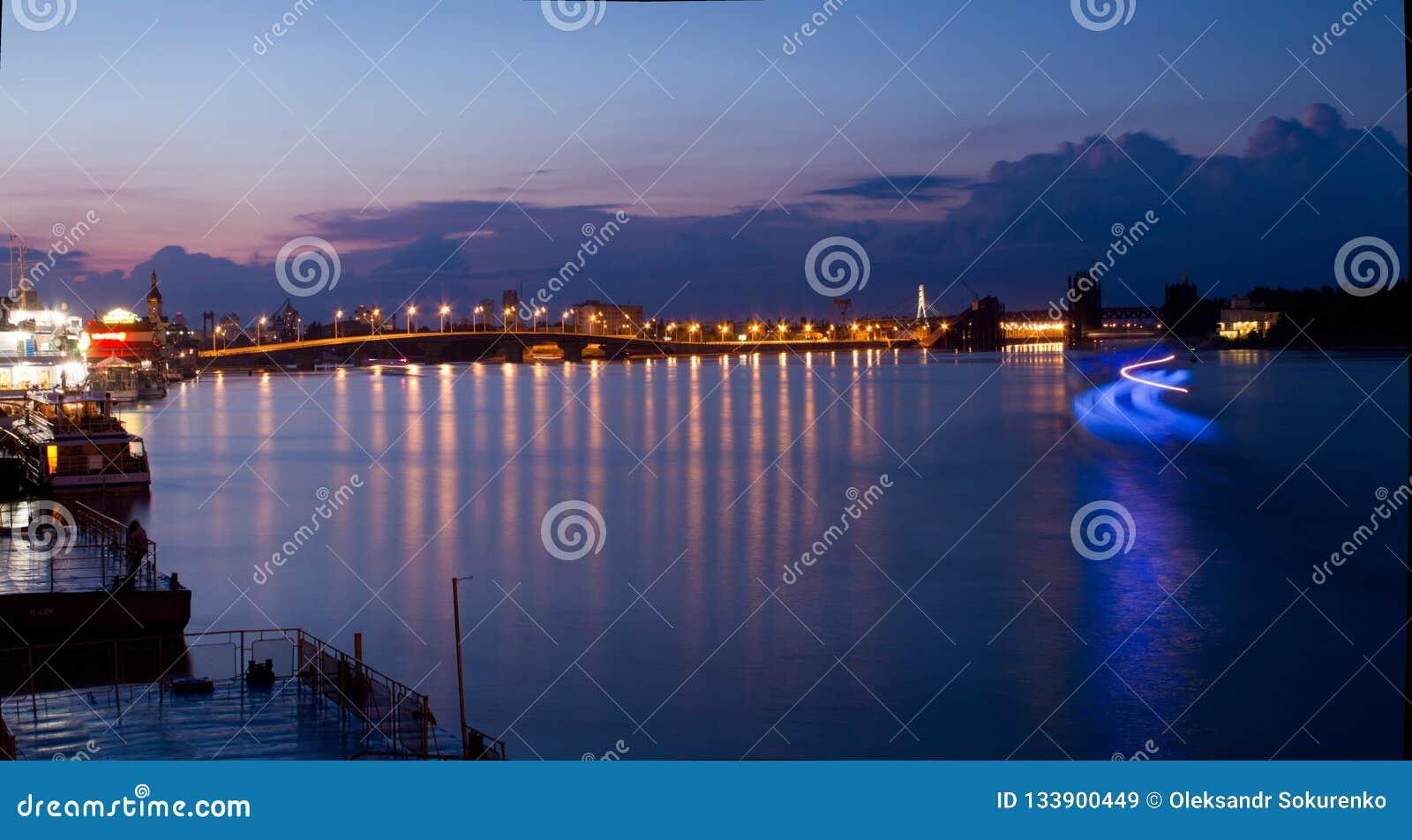 Muelle de Dnipro en fondo de la puesta del sol y