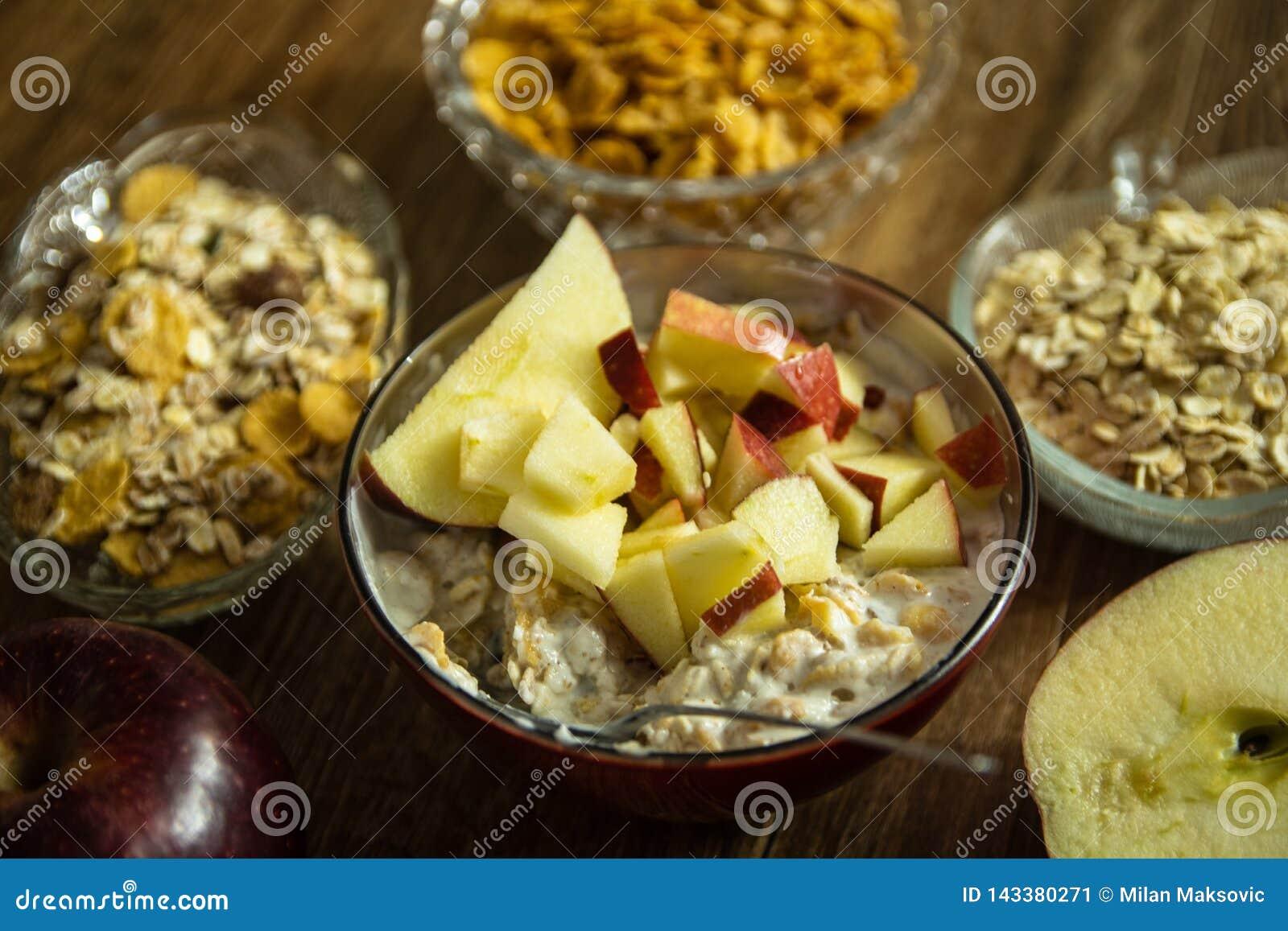 Muesli с сухофруктом, молоком и отрезанным красным яблоком на деревянном столе