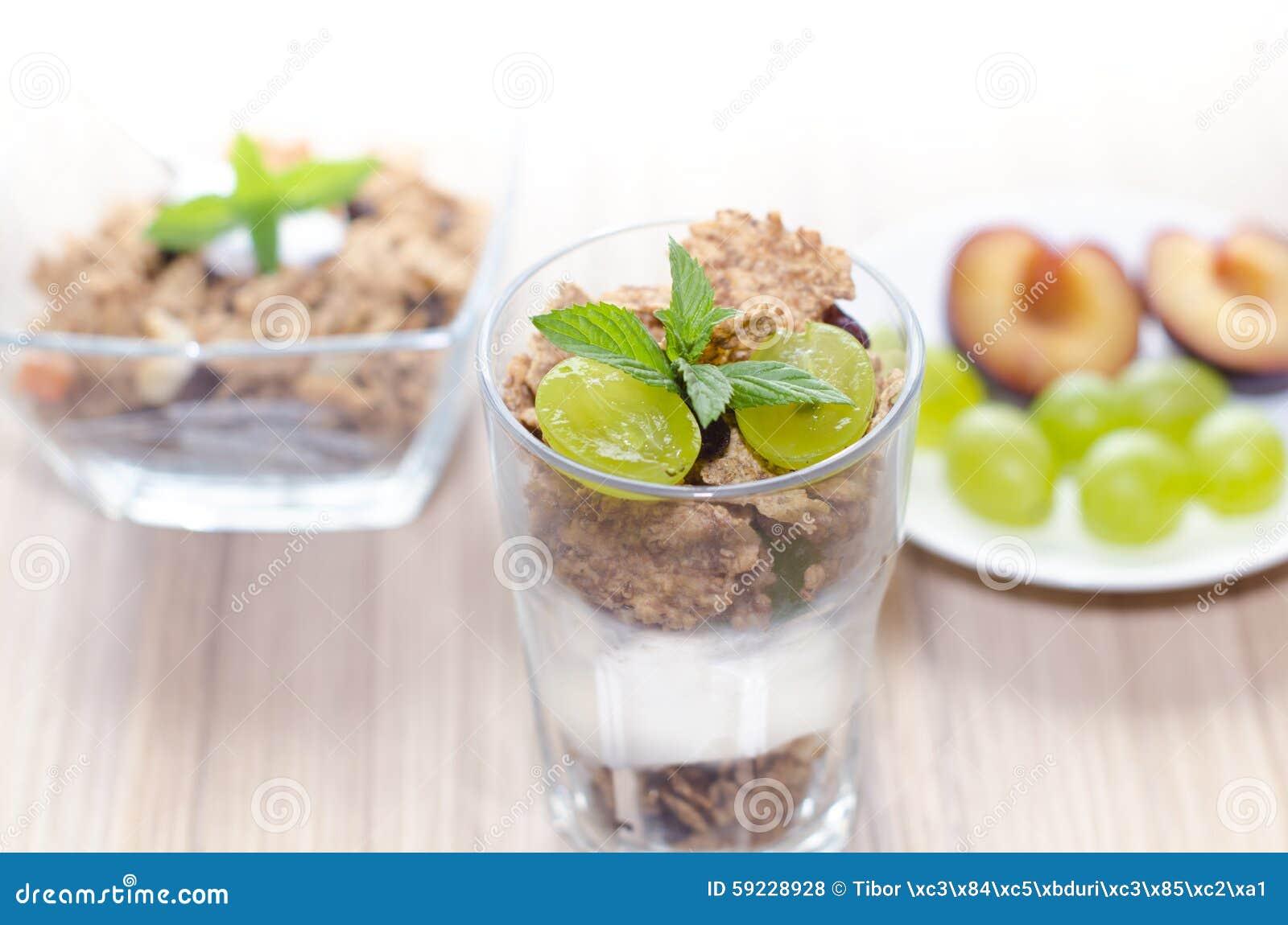 Muesli en un cuenco y un vidrio con el yogur, la menta y la fruta fresca