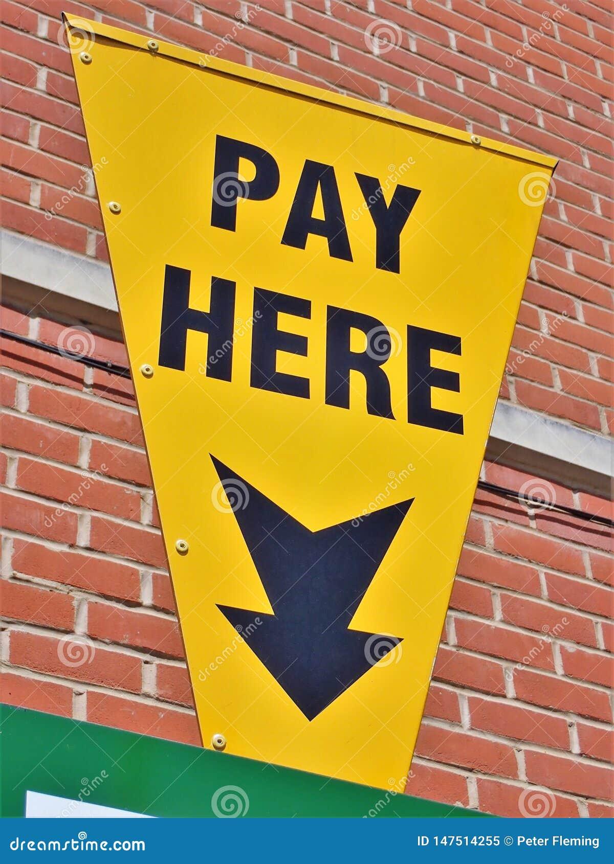 Muestra amarilla del aparcamiento con de la flecha y del texto una paga aquí