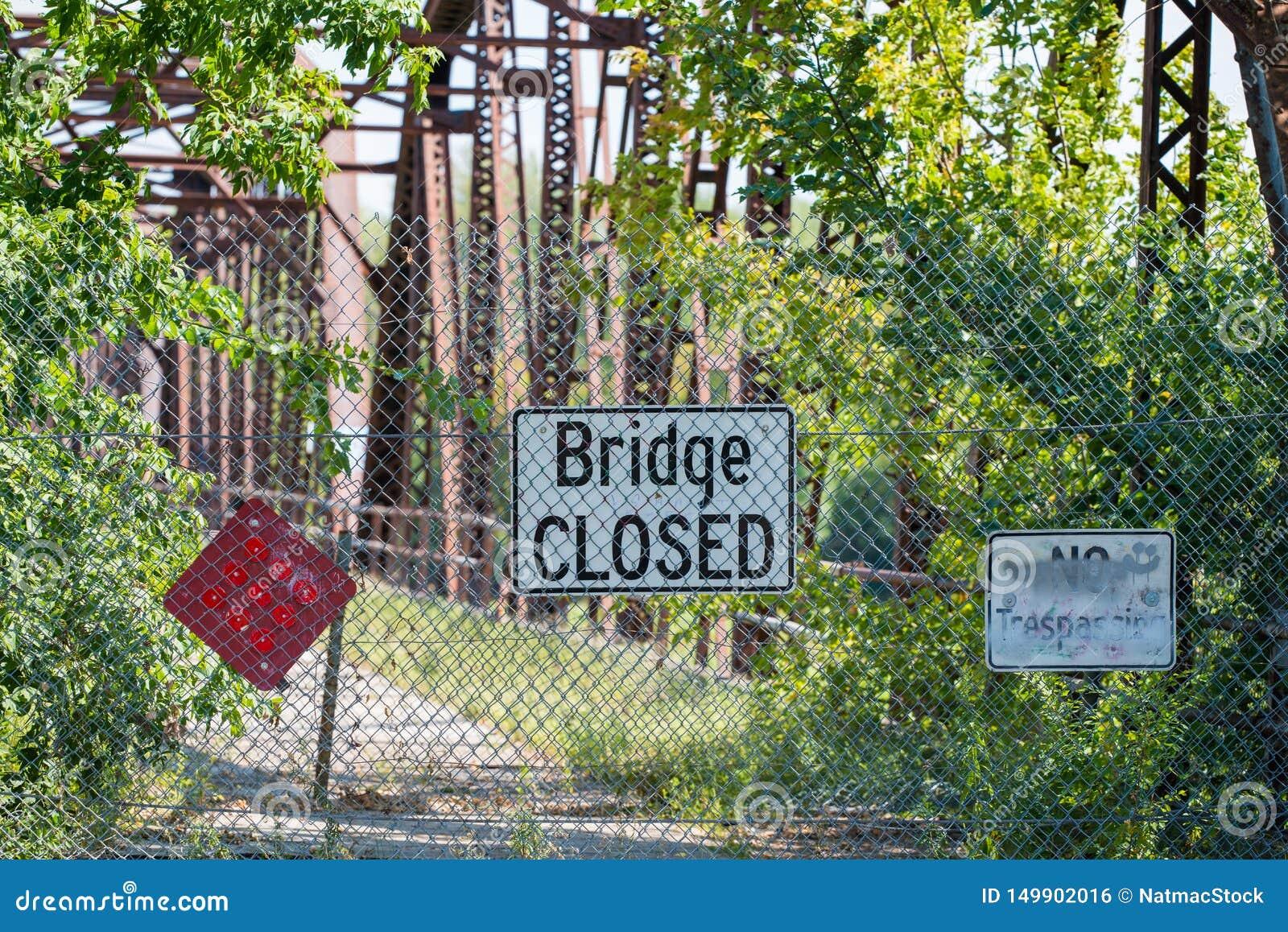 Muestra cerrada del puente delante del puente dilapidado con el crecimiento excesivo de árboles y de arbustos