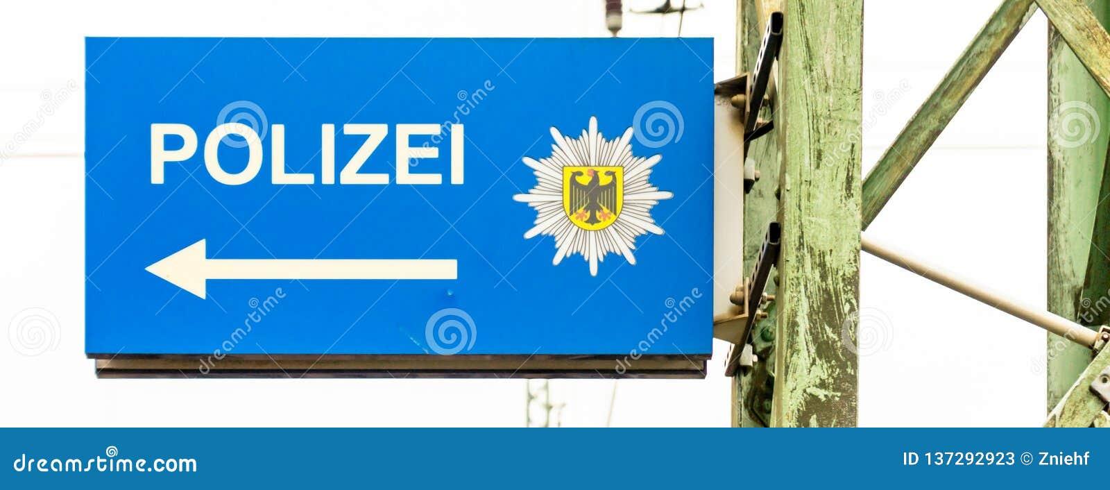 Muestra de la información para la comisaría de policía siguiente con una flecha blanca en una tierra azul y el escudo de armas de