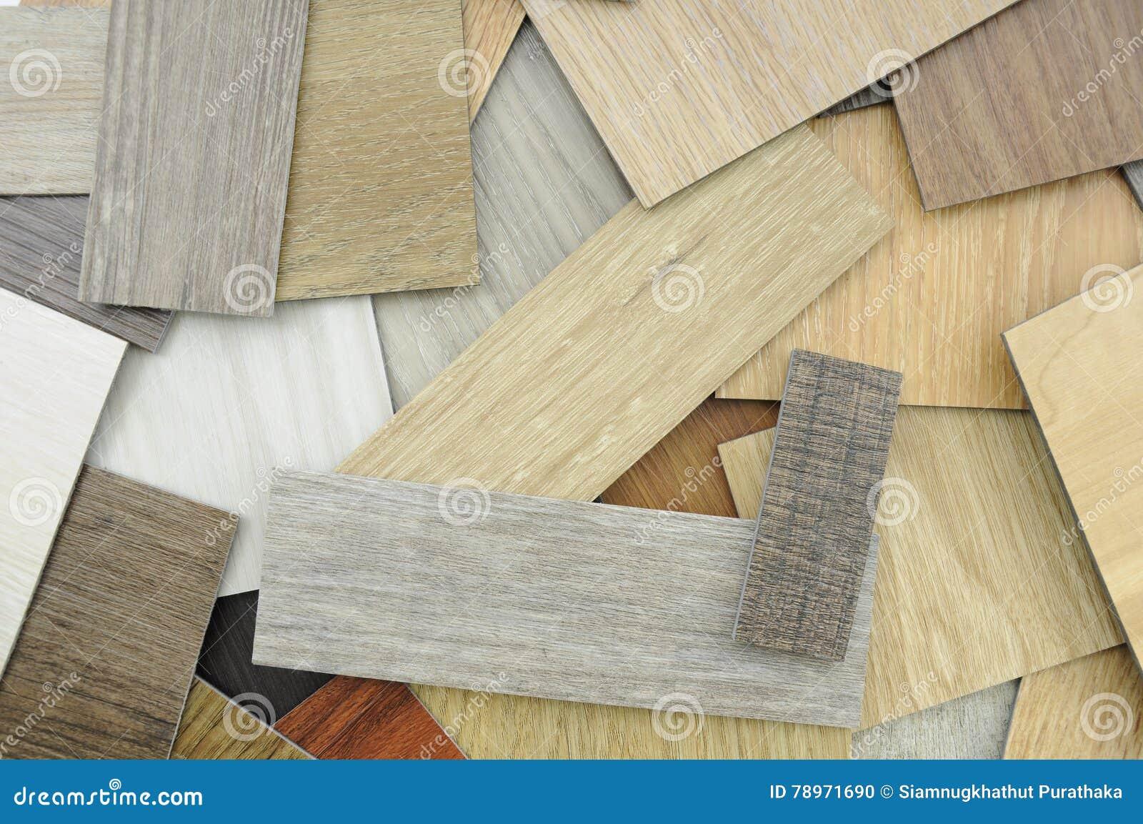 Muestras de baldosa de la lamina y del vinilo en Backgroun de madera