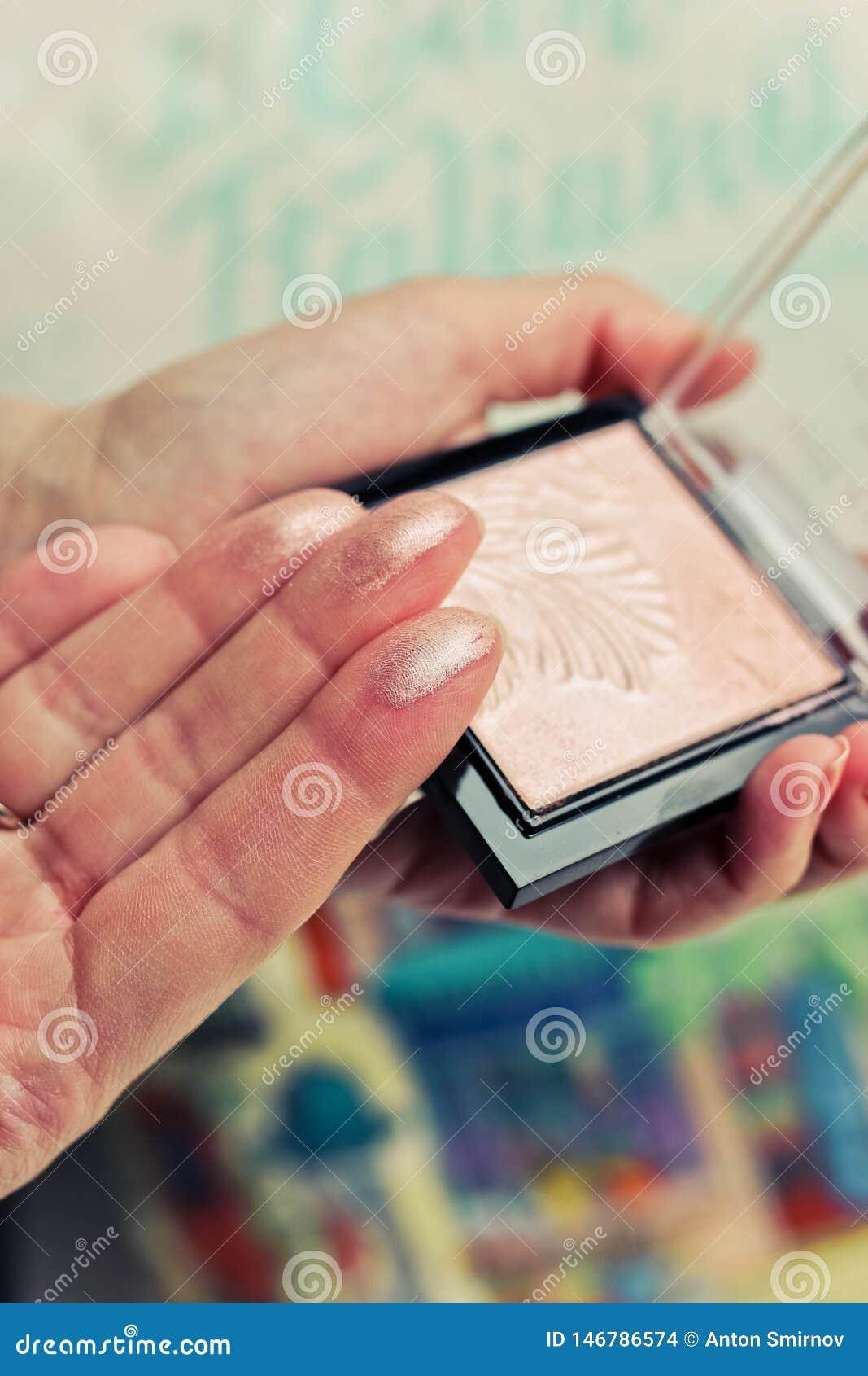 Muestras del polvo de cara en los fingeres y la paleta femeninos del polvo en fondo borroso colorido