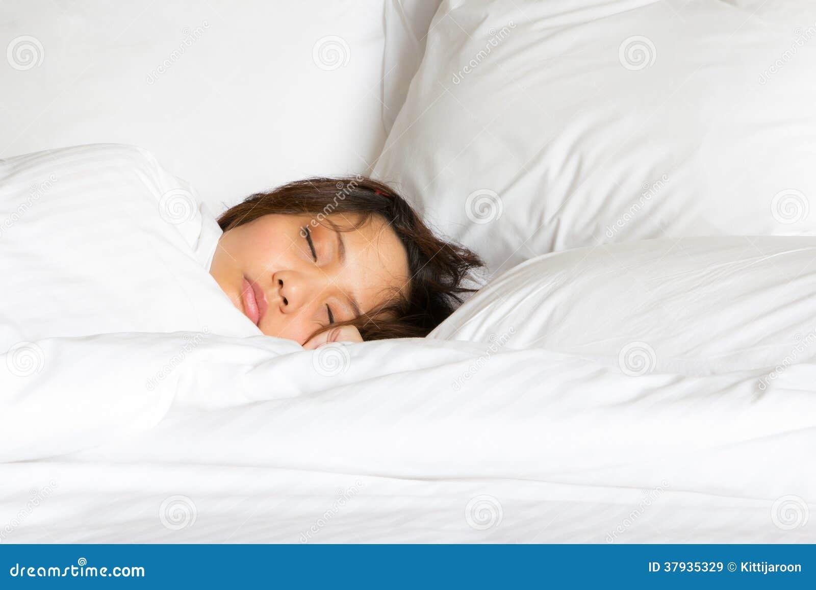 Muestre solamente a la mujer de la cara en sueño remetido la manta blanca en la cama