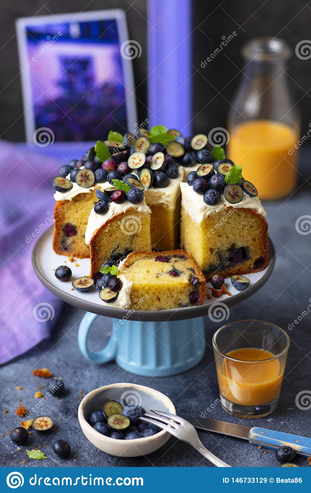 Muffin cake with cream cheese frosting and blueberries