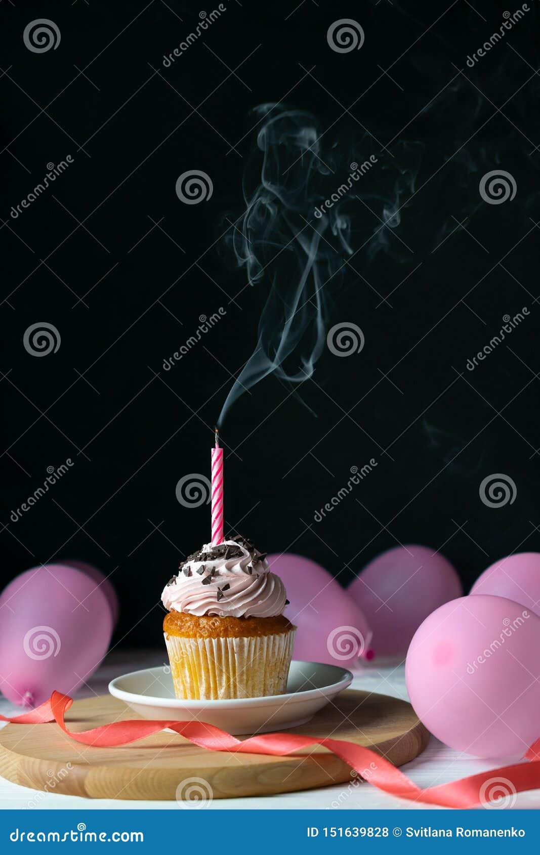 Muffin för lycklig födelsedag med en stearinljus som ut blåsas på en svart bakgrund med ballonger