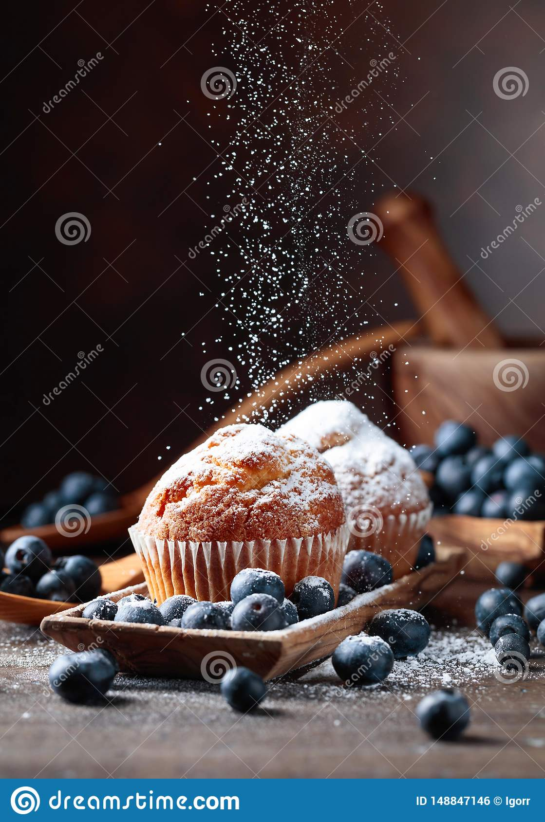 Muffins and blueberries sprinkled with powdered sugar