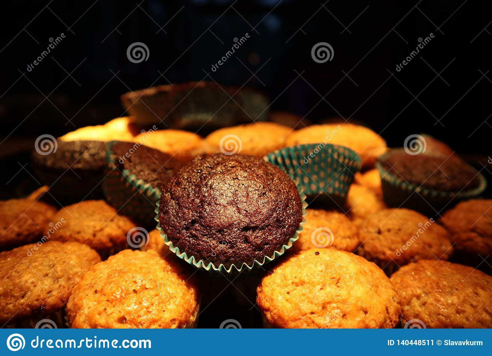 Muffins with chocolate and nuts. in the background a cook in an apron