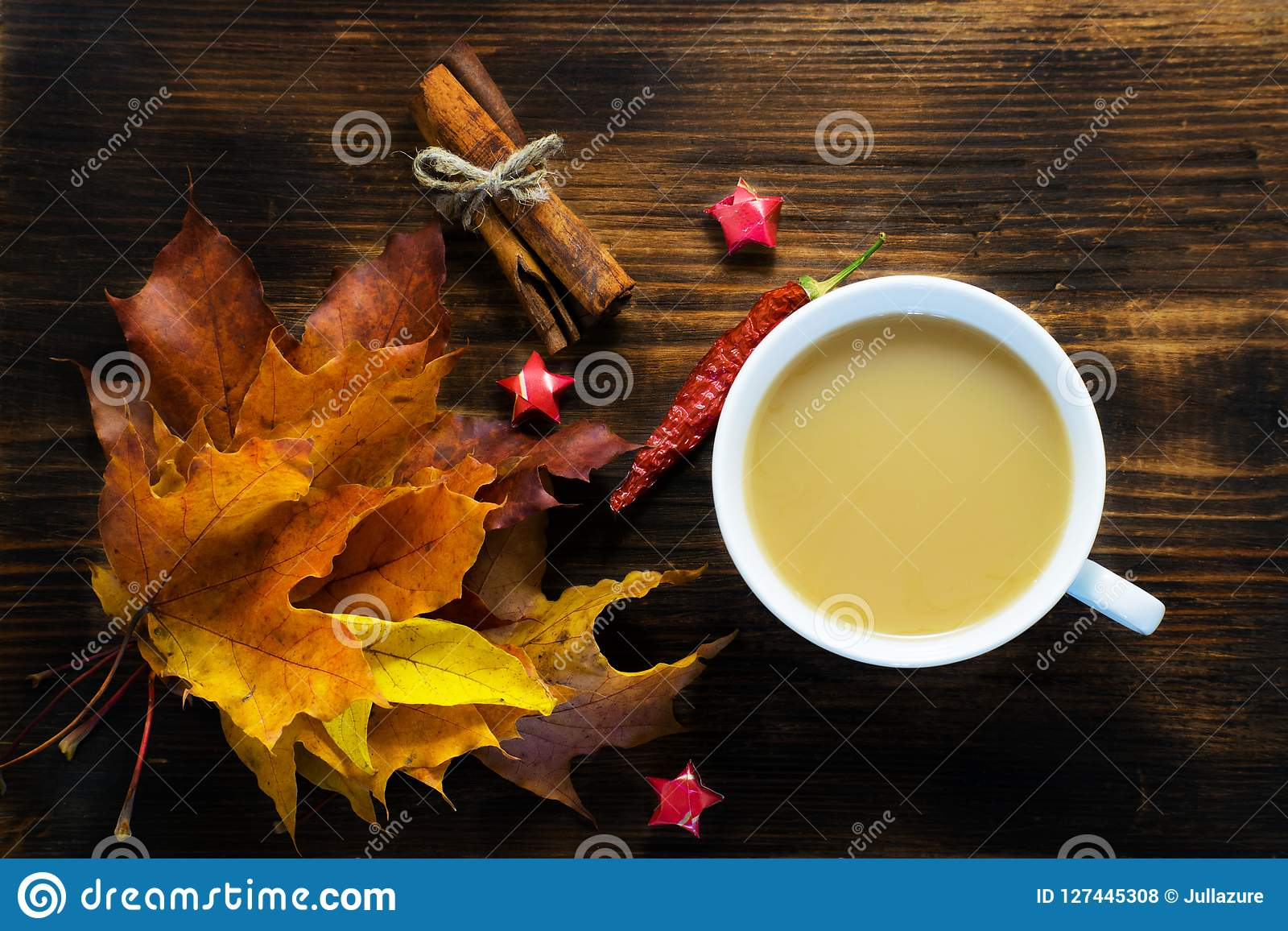 Mug of hot coffee with milk and spices and autumn leaves on wooden table. Morning cup of cappuccino coffee with cinnamon and maple