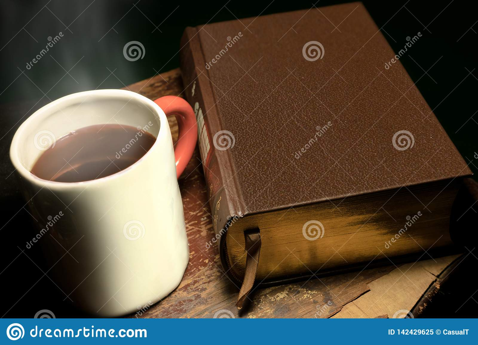 A mug with steaming hot tea or coffee placed next to a big leather-bound book, on an old and worn wooden table