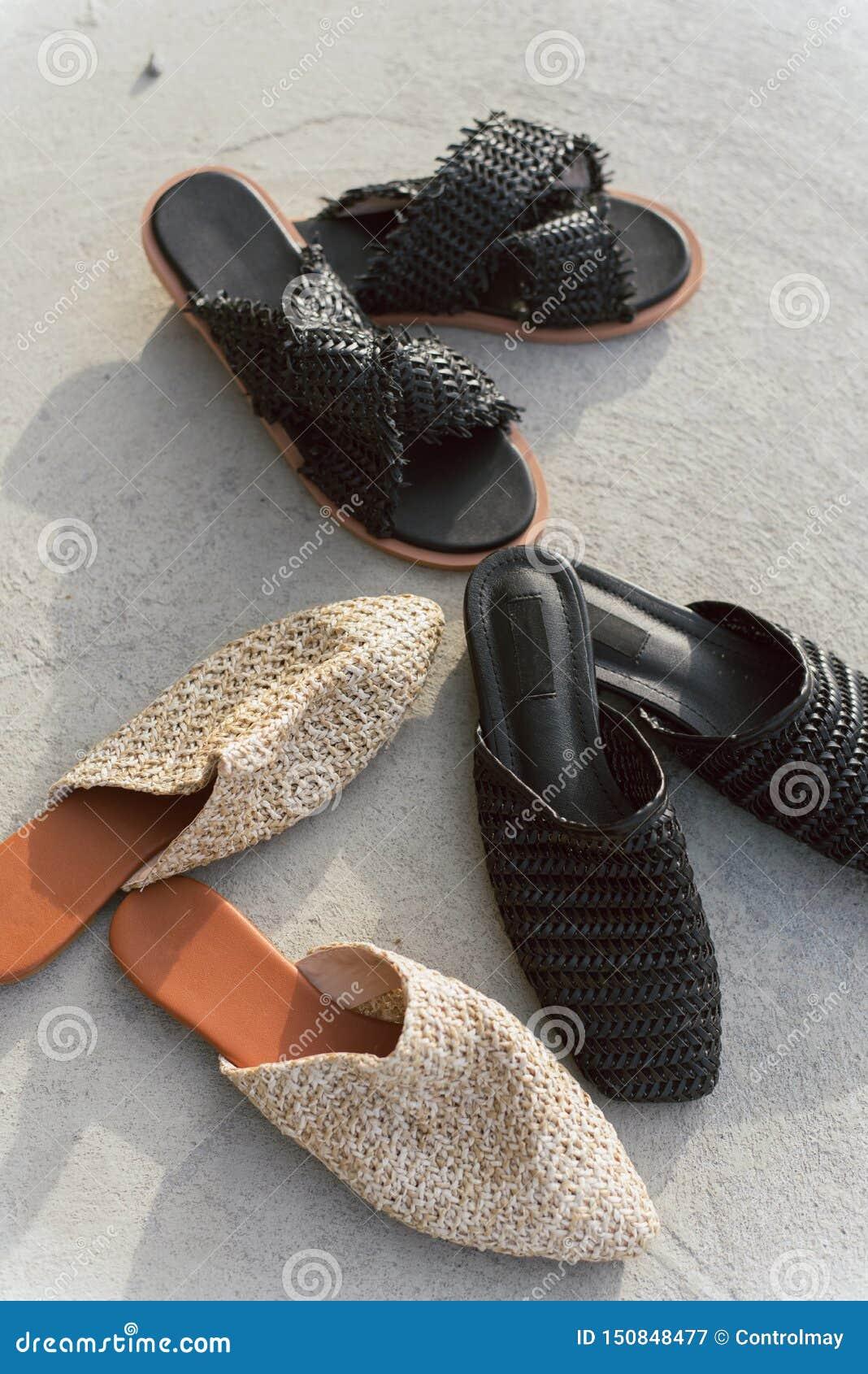 Muitas sapatas tecidas diferentes em um fundo concreto cinzento Ardósias e mulas pretas e bege elegante e à moda diferentes