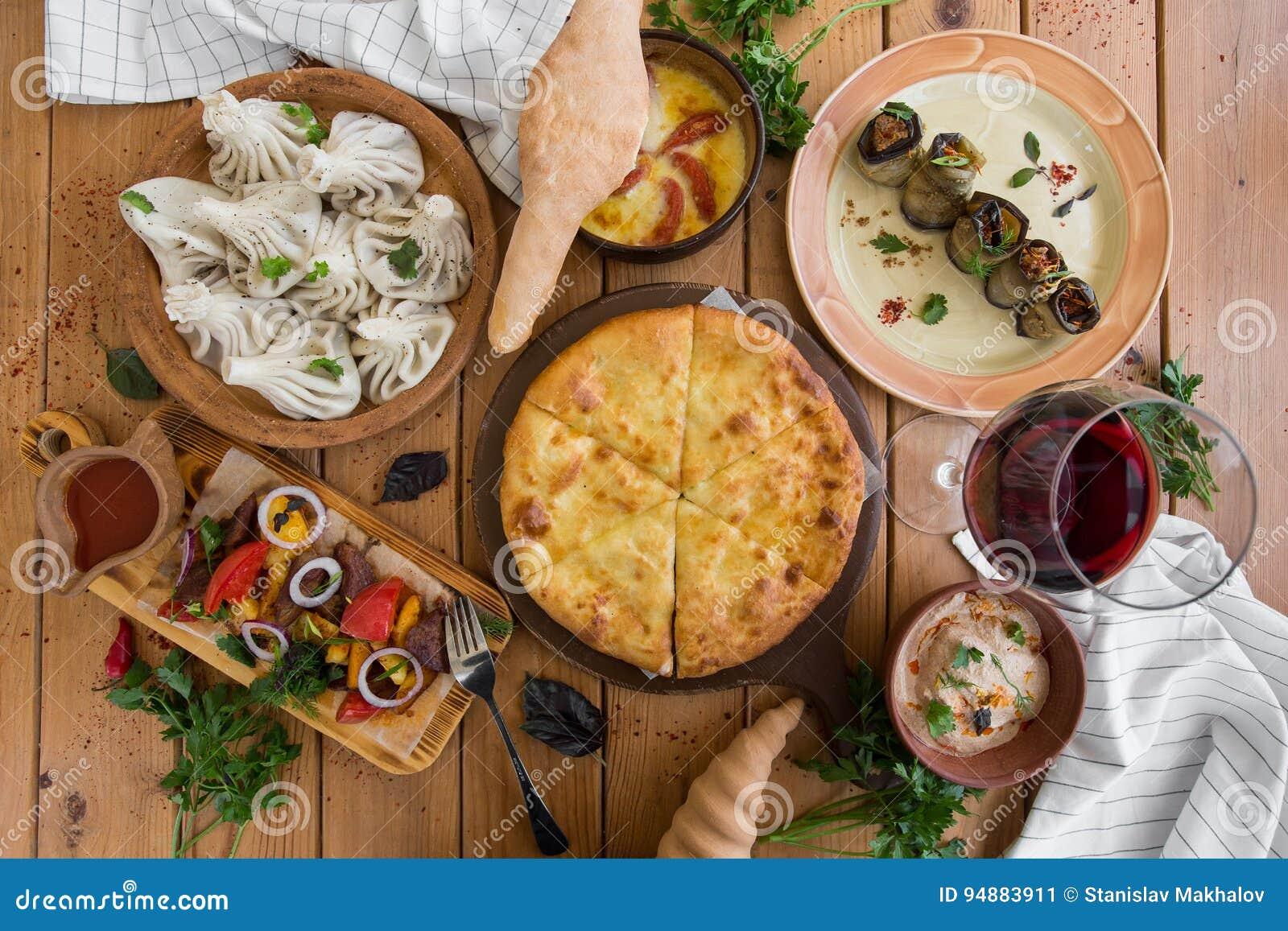 Muito alimento na tabela de madeira Culinária Georgian Vista superior Configuração lisa Khinkali e pratos Georgian
