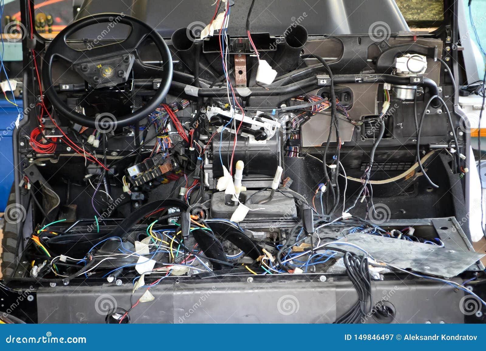 Muito embaraçar fios coloridos da fiação do carro encontra-se na cabine do carro desmontado com conectores e tomadas, uma vista