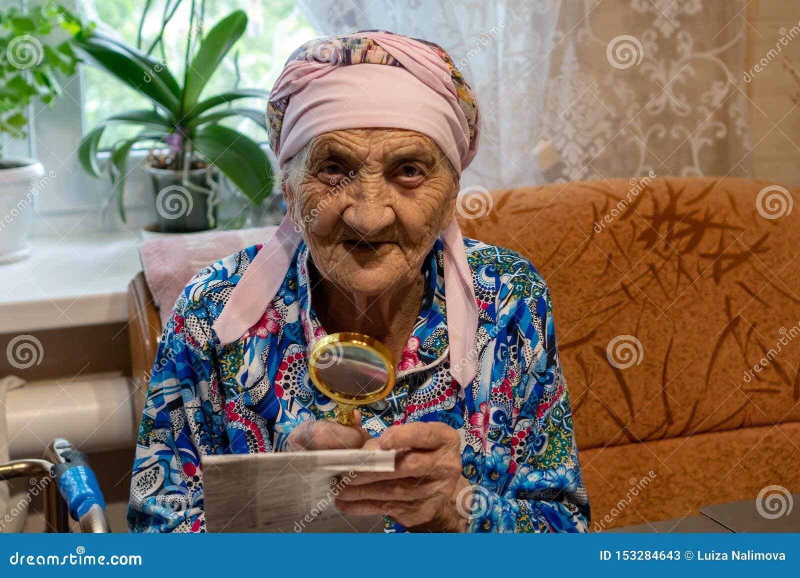 Muito mulher adulta com a lente de aumento que tenta ler de um jornal a avó 90 anos velha lê na tabela com lente de aumento A