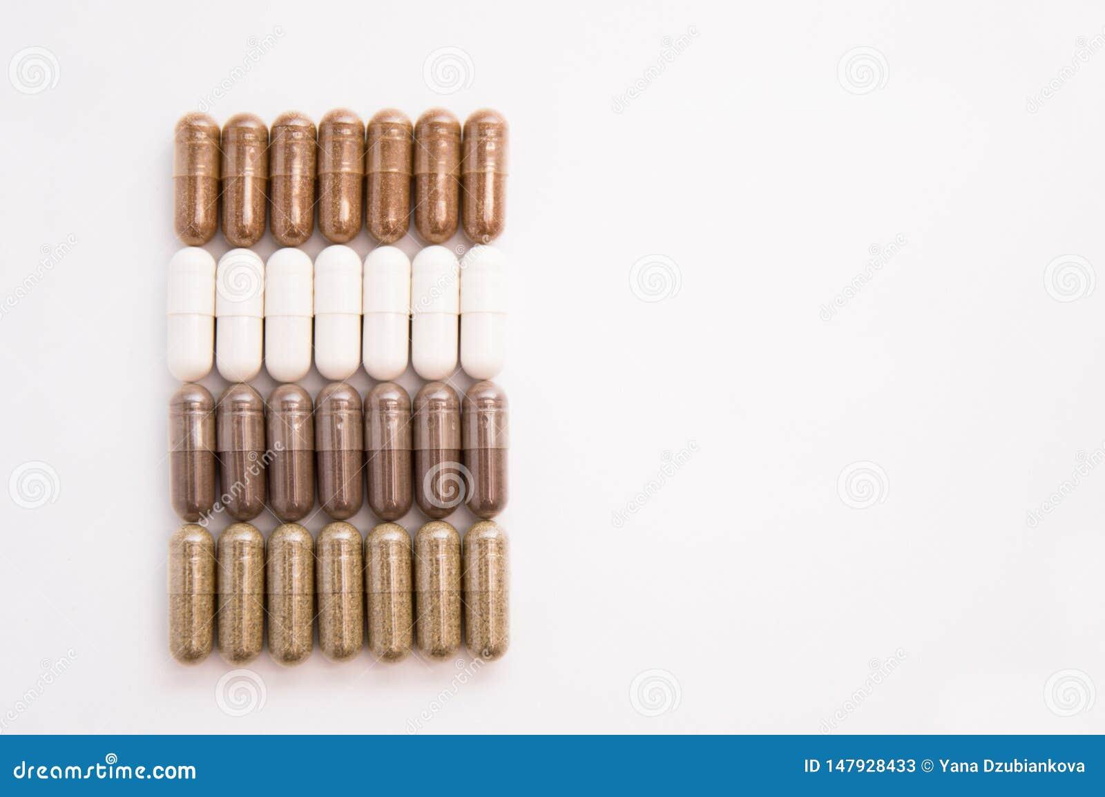 Muitos comprimidos da c?psula derramados fora de um frasco em um fundo branco