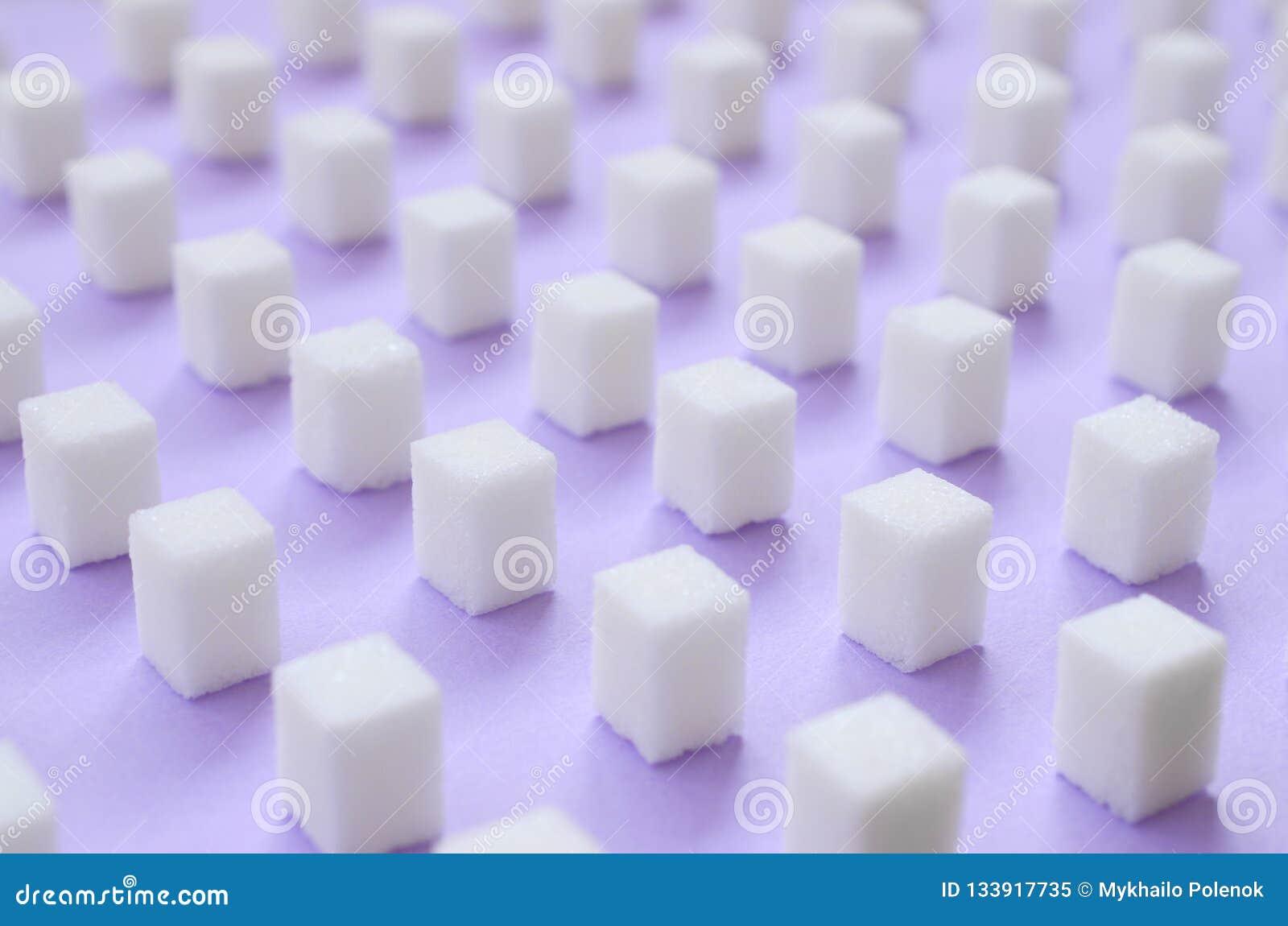 Muitos cubos pequenos do açúcar são alinhados em um fundo violeta