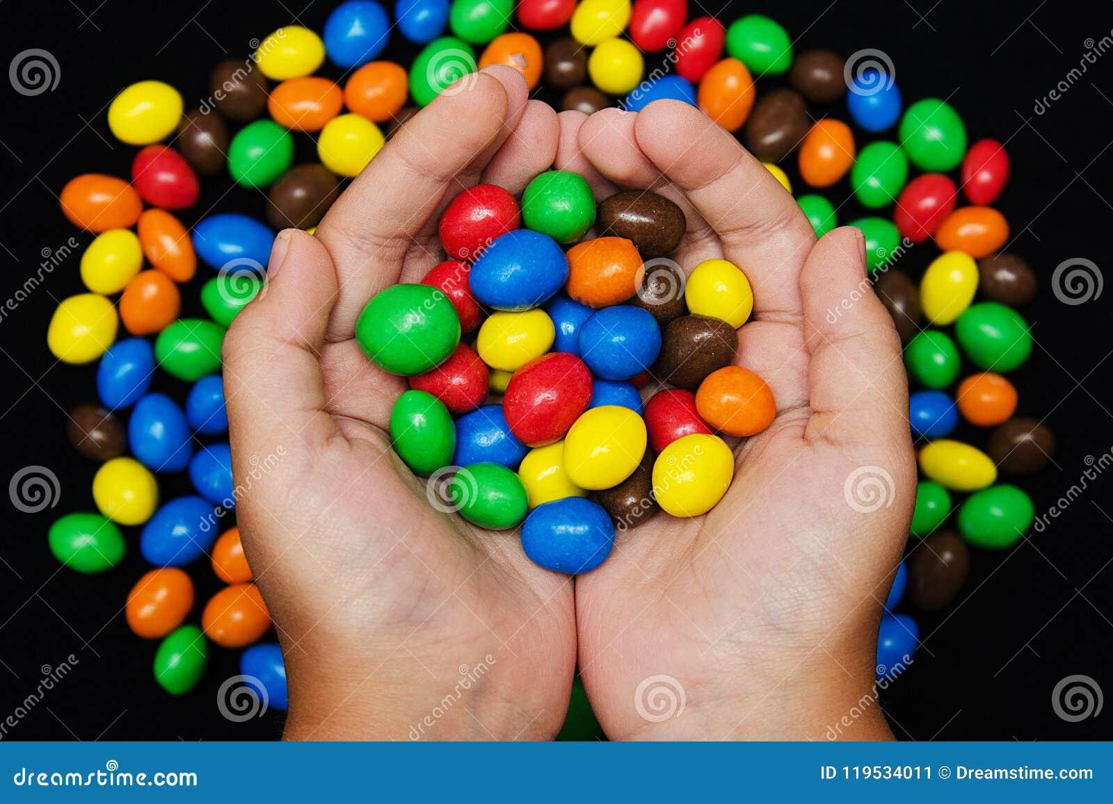 Muitos doces nas mãos do ` s das crianças, vista superior da cor