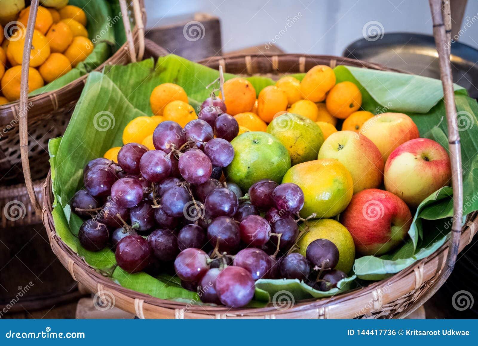 Muitos frutos na folha da banana na cesta de bambu