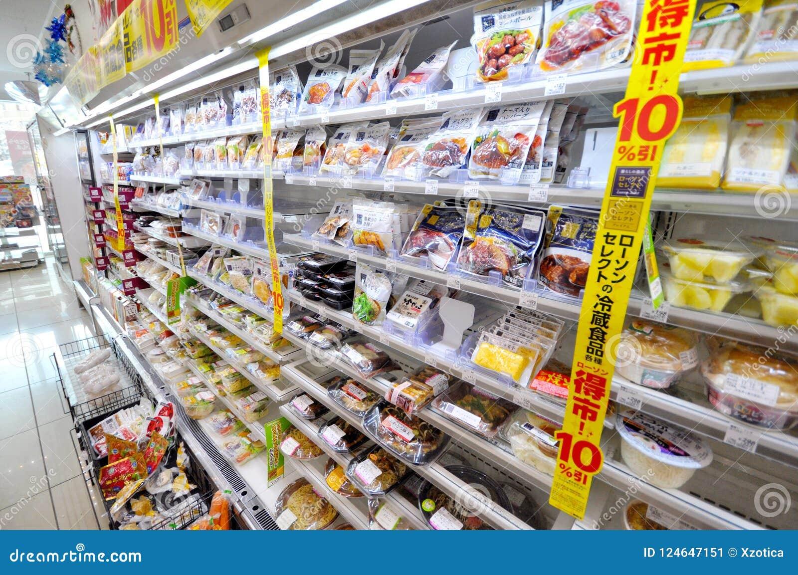 Muitos tipos dos alimentos em prateleiras no supermercado japonês em Sappor