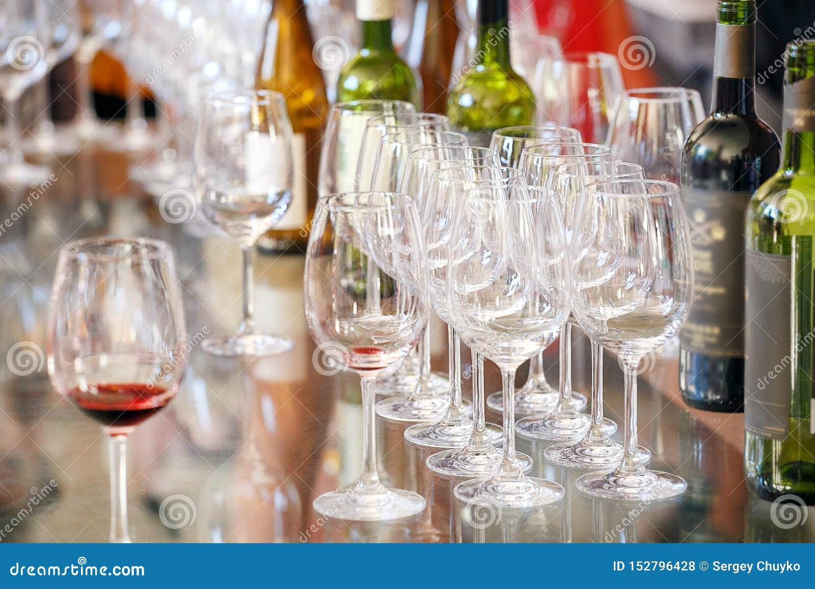 Muitos vidros e garrafas do vinho diferente em uma tabela