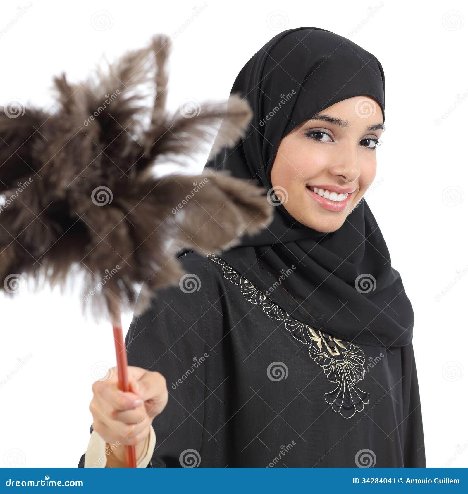 Mujer árabe del ama de casa que sonríe y que sostiene un plumero limpio