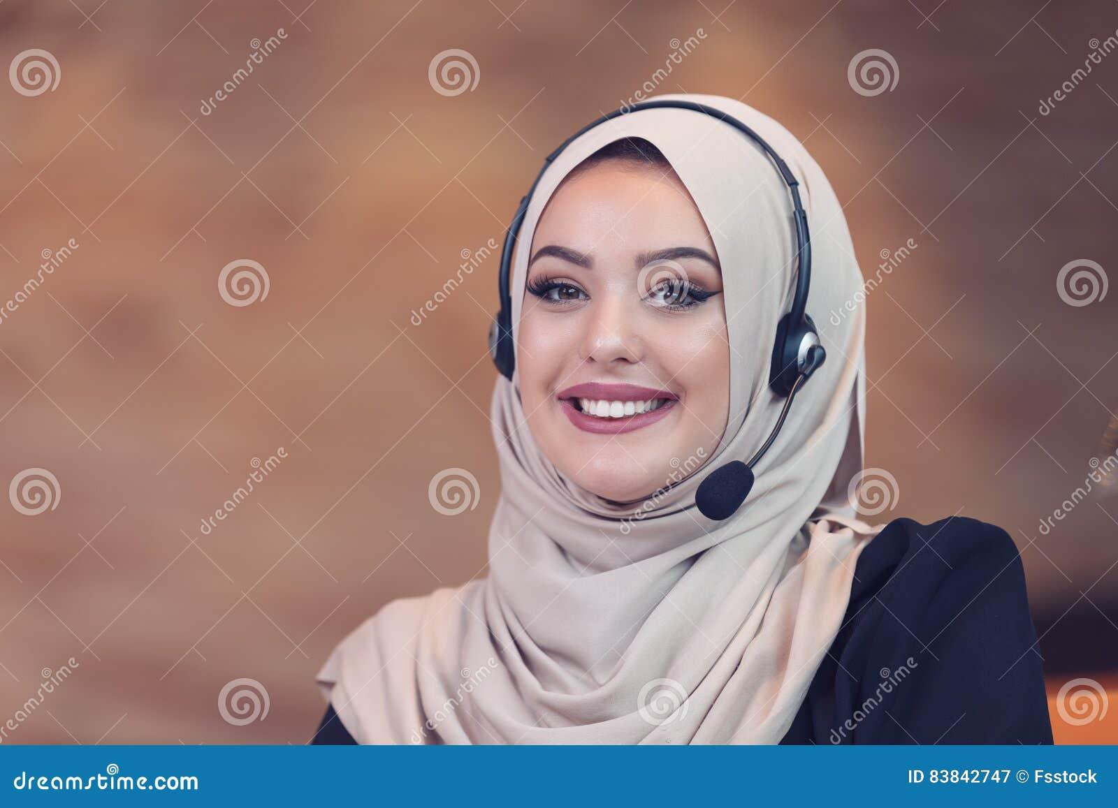 Mujer árabe del operador hermoso del teléfono que trabaja en oficina de lanzamiento