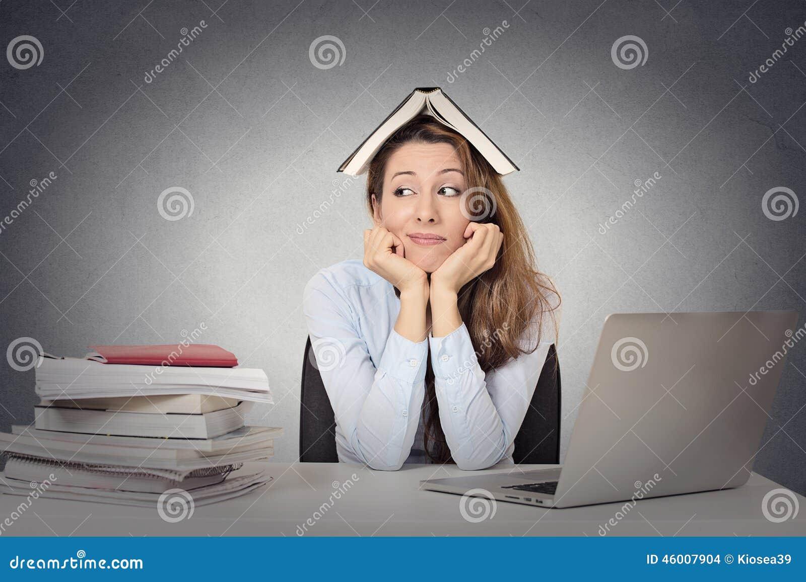Mujer aburrida, estudiante de mirada divertido con el libro en la cabeza