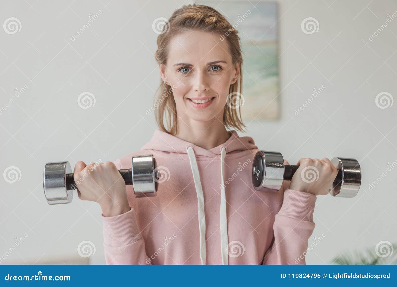 Mujer adulta hermosa que se resuelve con pesas de gimnasia