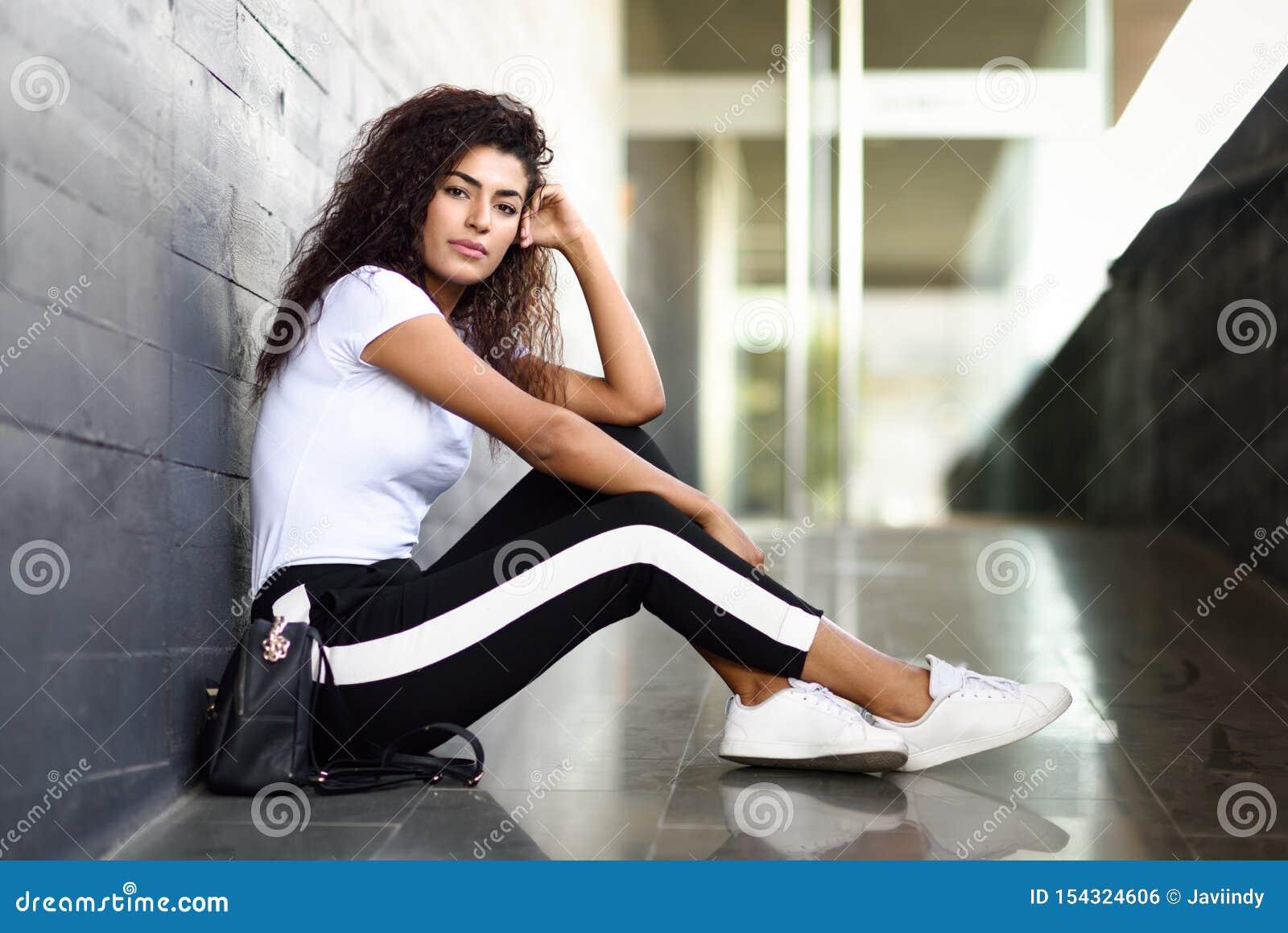 Mujer africana con el peinado rizado negro que se sienta en piso urbano