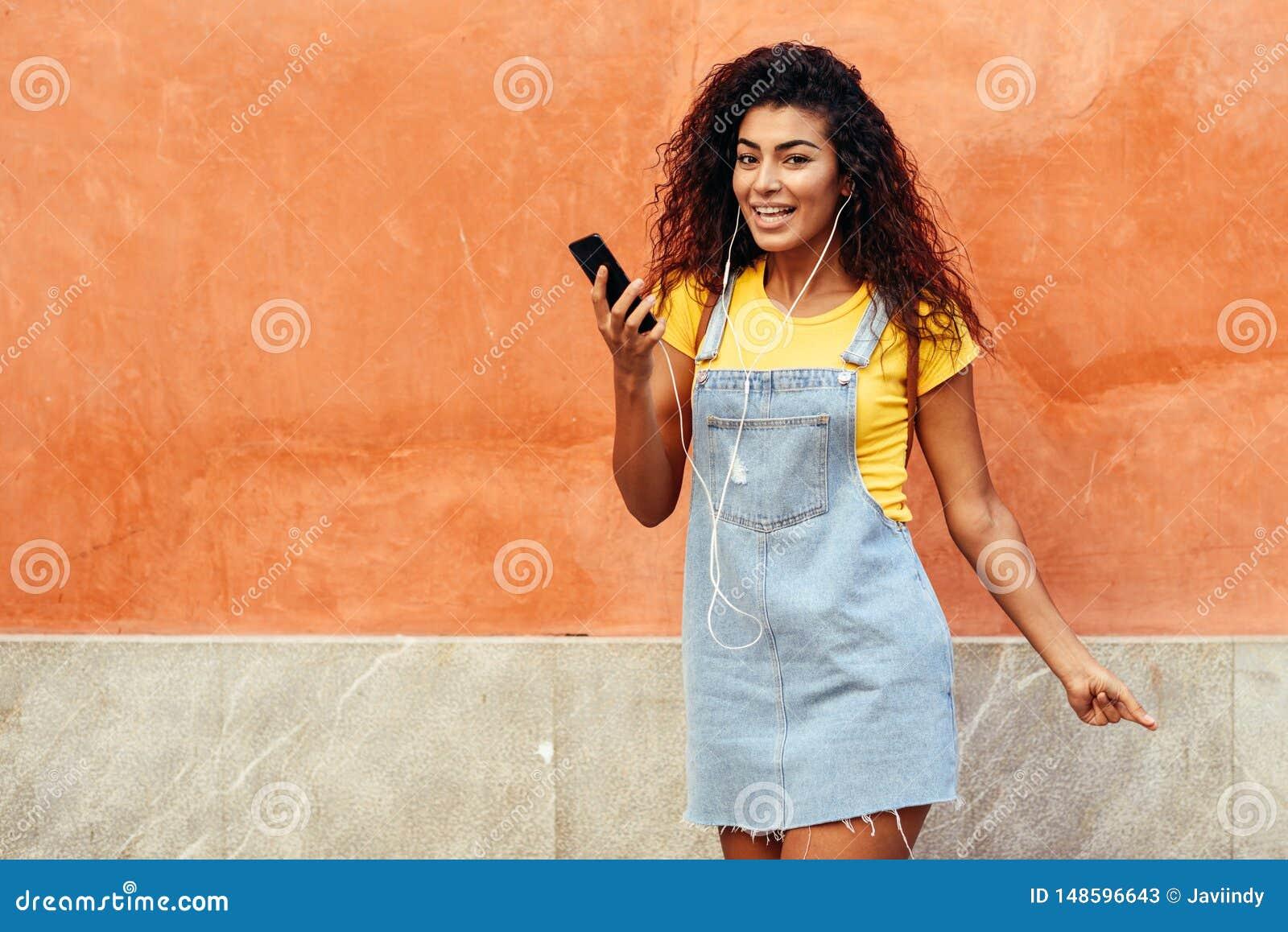 Mujer africana del norte feliz que escucha la m?sica con los auriculares