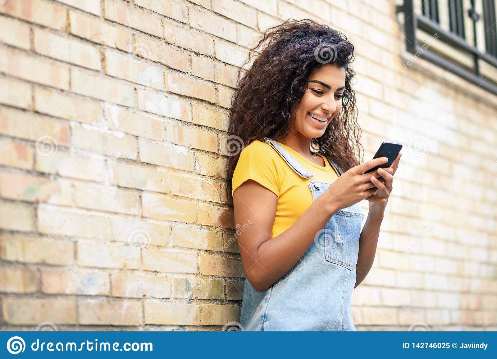 Mujer africana del norte joven que manda un SMS con su teléfono elegante al aire libre