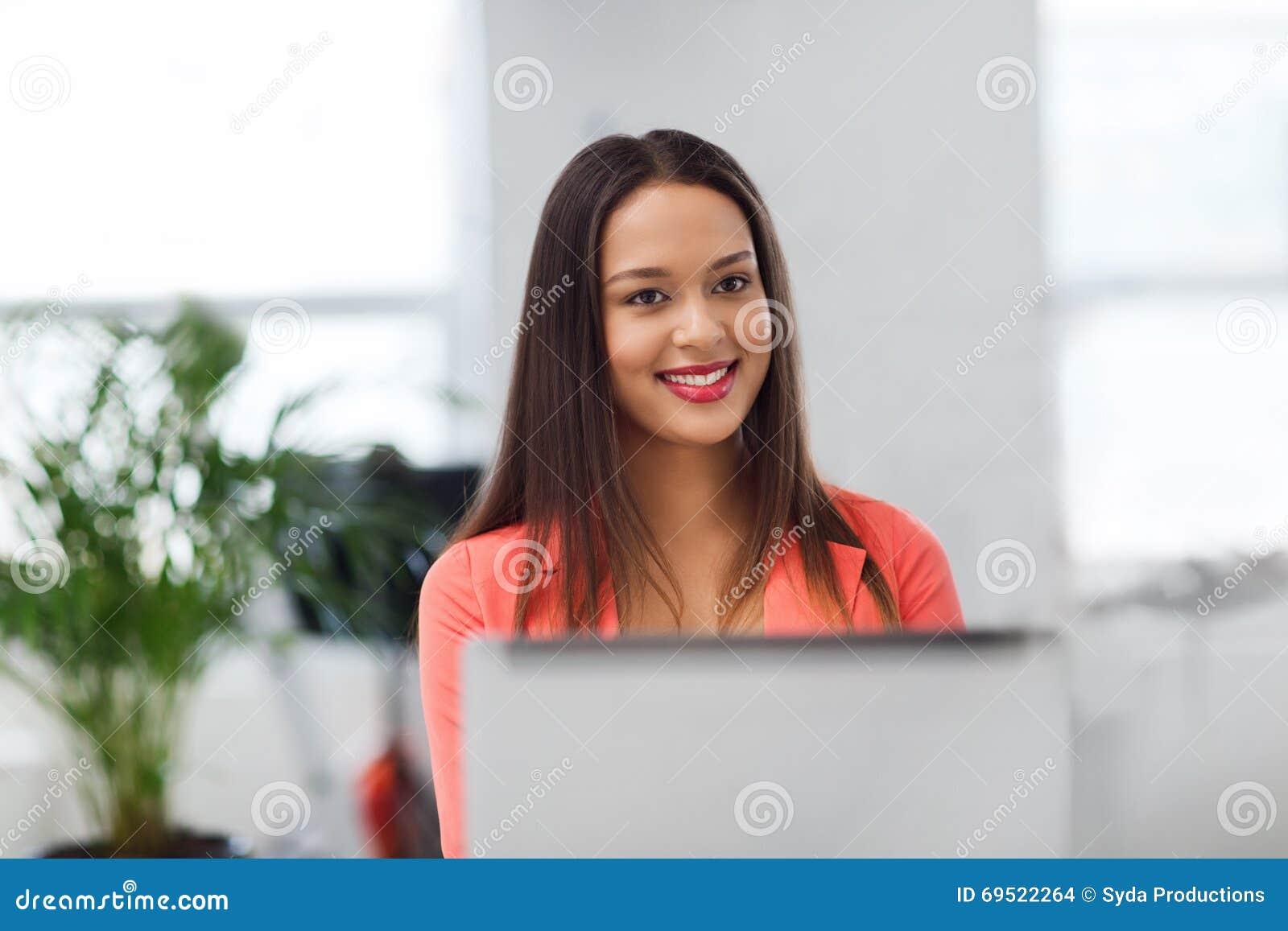 Mujer africana feliz con el ordenador portátil en la oficina