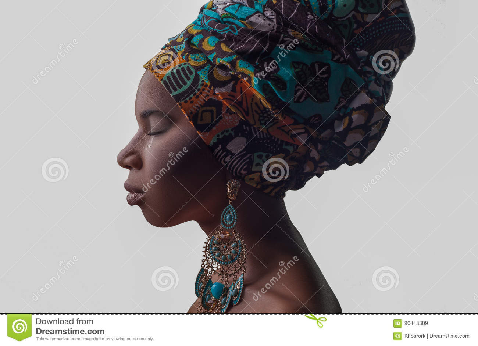 Mujer africana hermosa joven en estilo tradicional con la bufanda, pendientes llorando, aislada en fondo gris