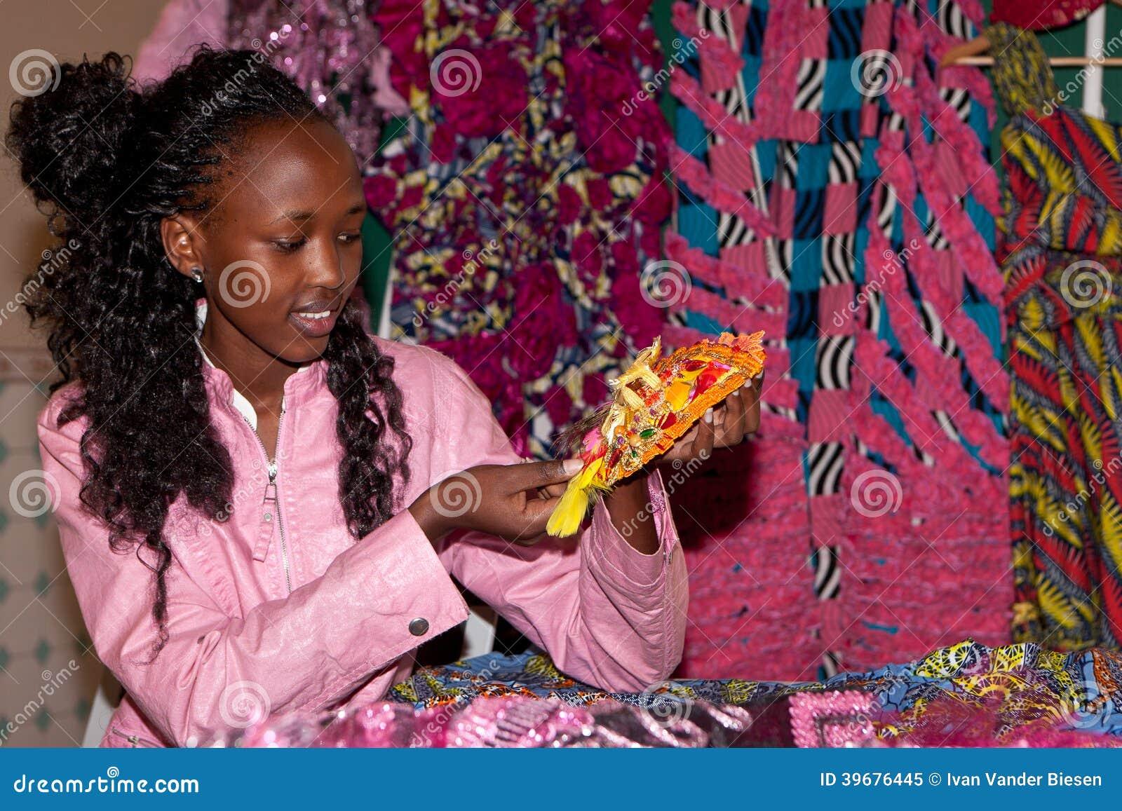 Mujer africana que muestra gotas y telas amarillas