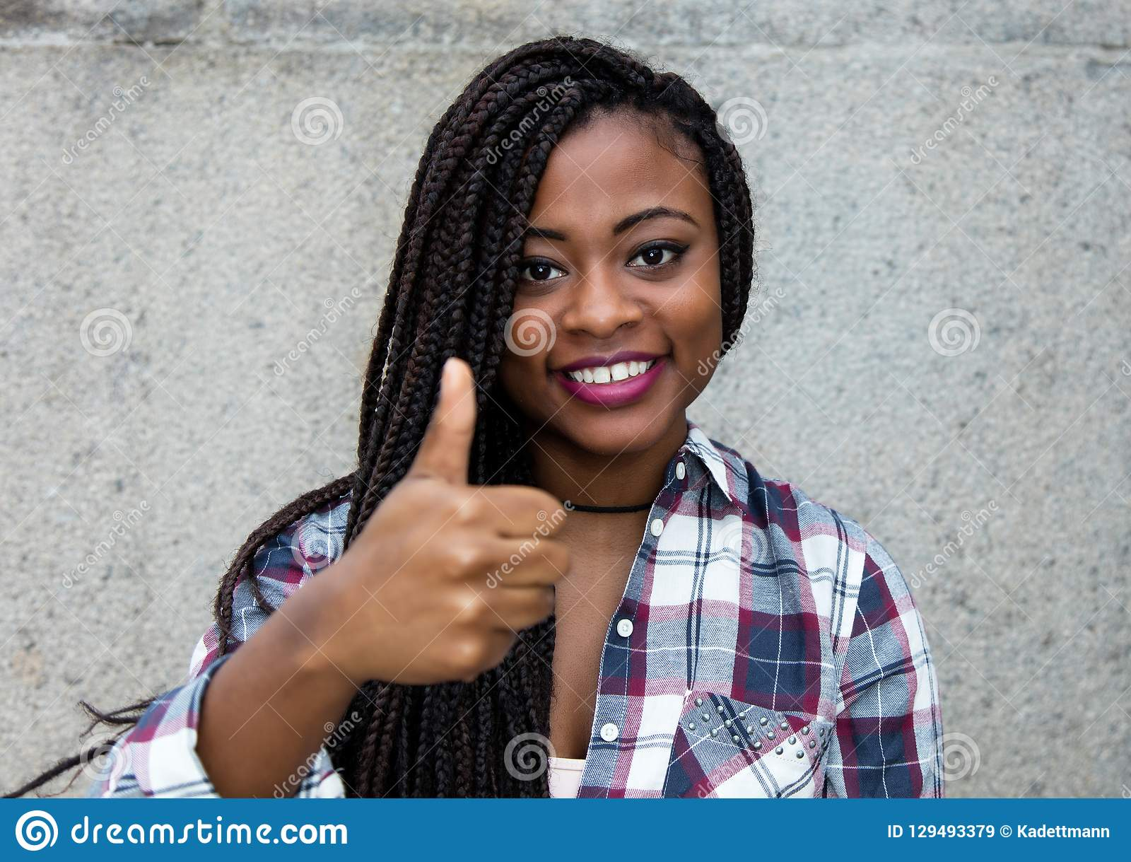 Mujer afroamericana de risa con los dreadlocks que muestran el pulgar para arriba