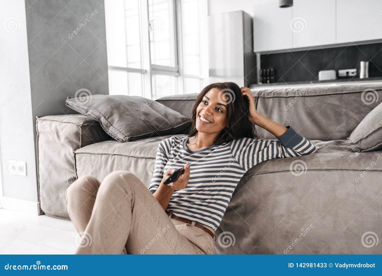 Mujer afroamericana joven atractiva que se sienta en un sofá