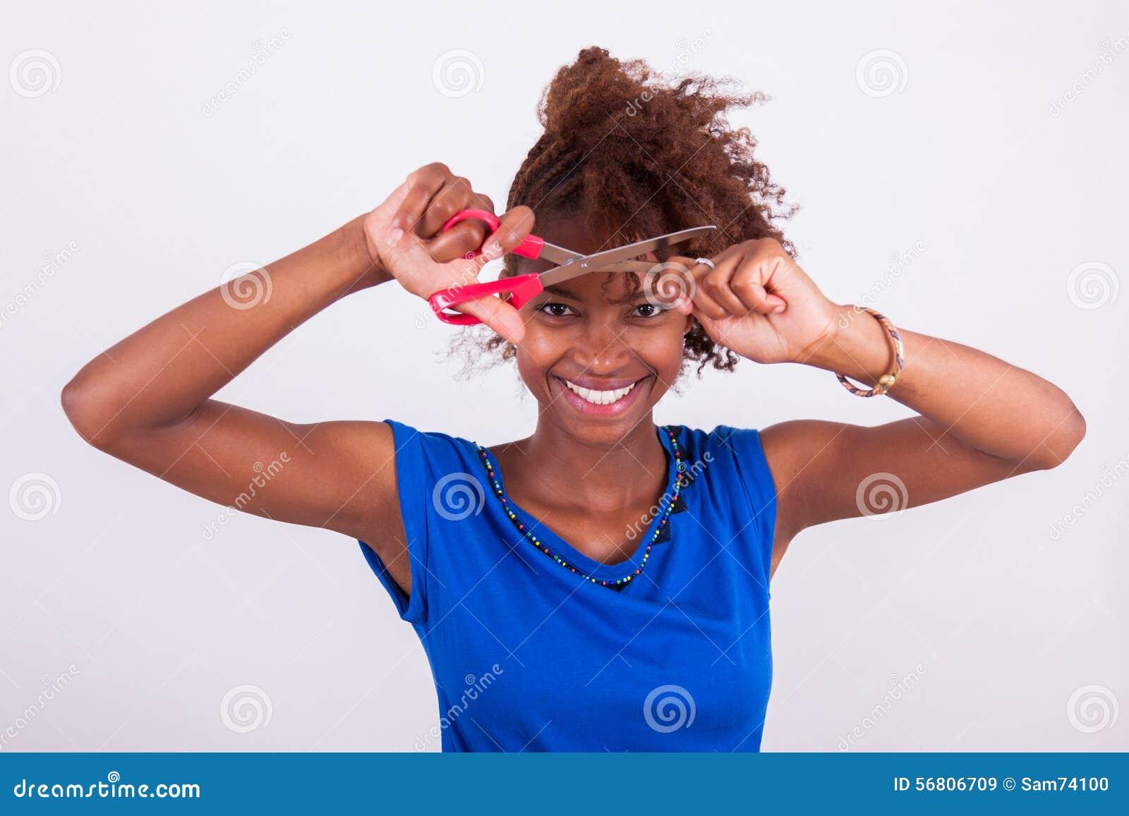 Mujer afroamericana joven que corta su pelo afro muy rizado con s