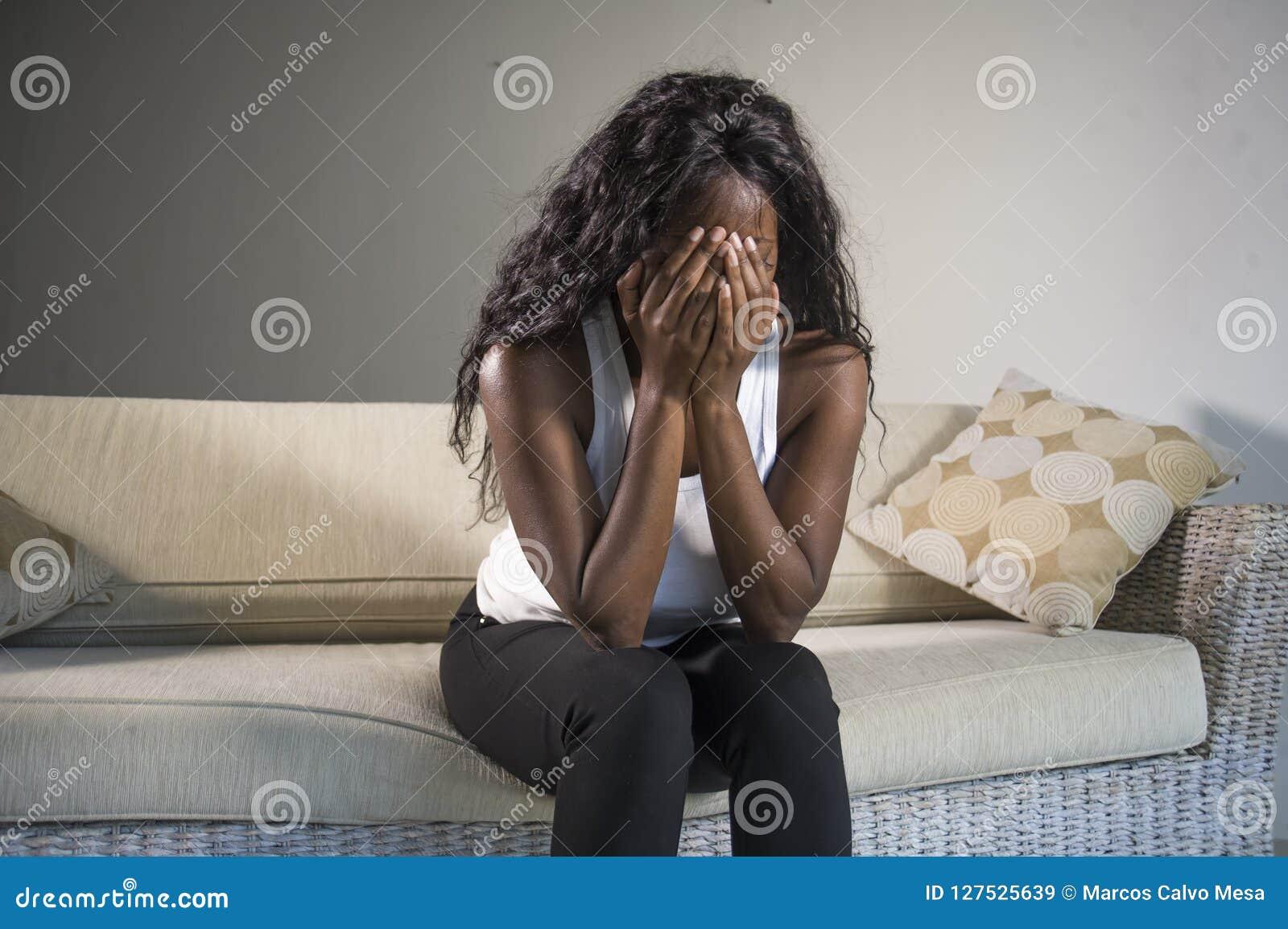 Mujer afroamericana negra atractiva y triste joven que sienta en casa las sensaciones presionadas del sofá del sofá ansiosas y su