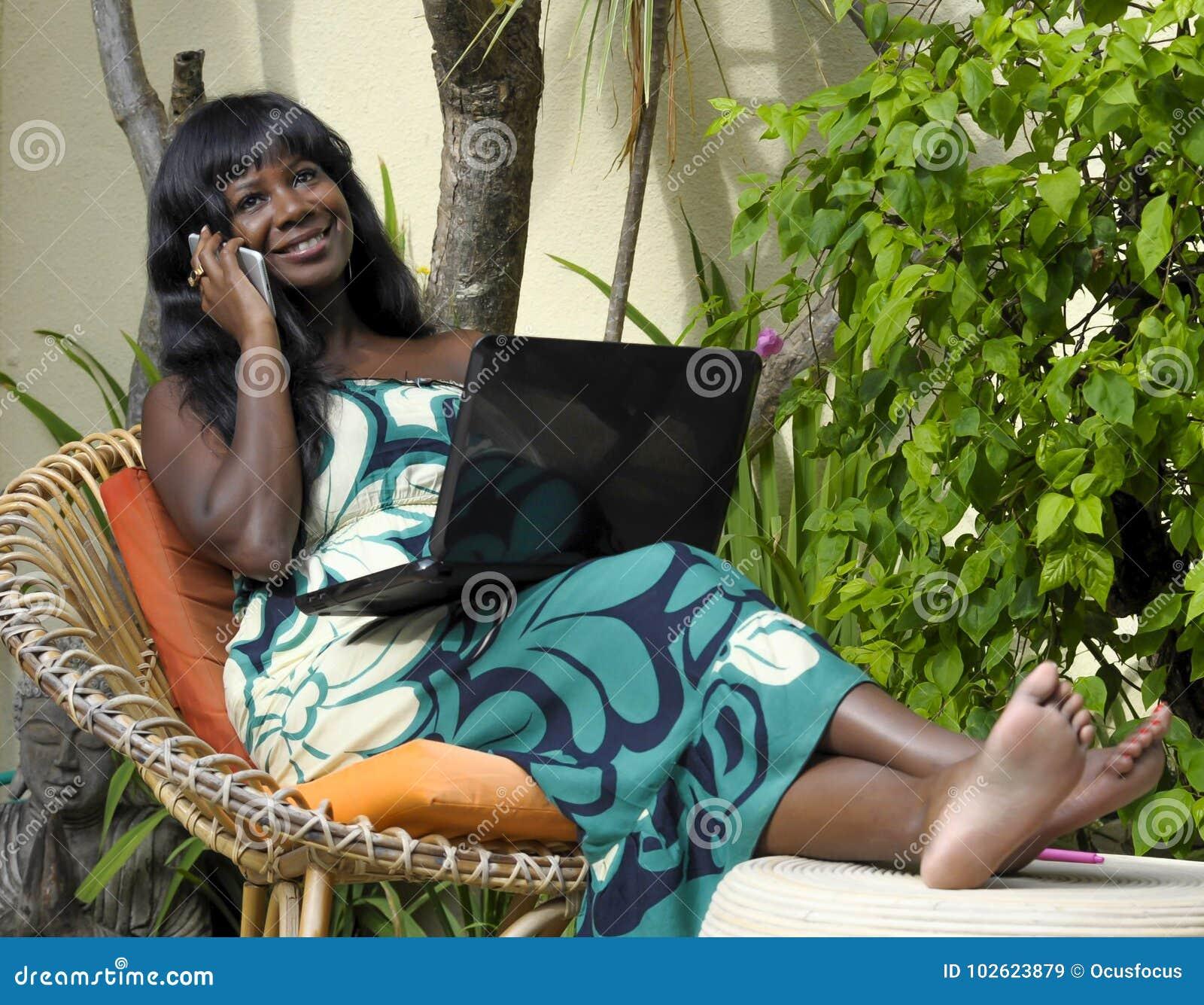 Mujer afroamericana negra feliz en el vestido elegante que trabaja en el chalet de lujo de la terraza con el ordenador portátil q